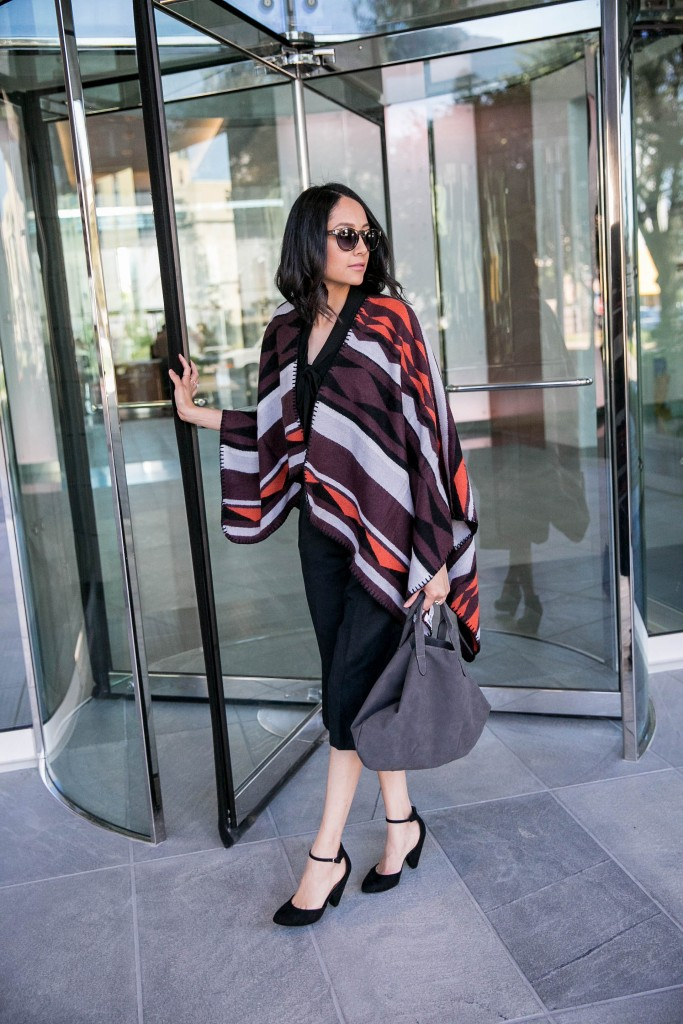 Daily Craving wearing a fall look with black culotte pants and a printed poncho