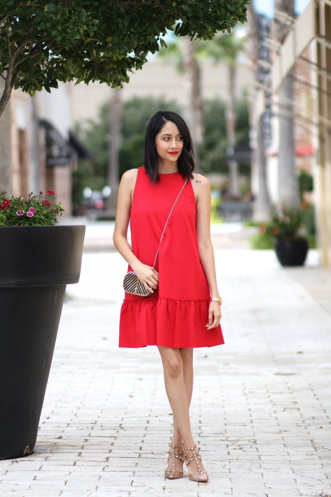 Style blogger Daily Craving wearing a red dress with a ruffle hem