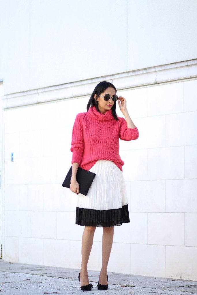 Pink turtleneck sweater and pleated skirt