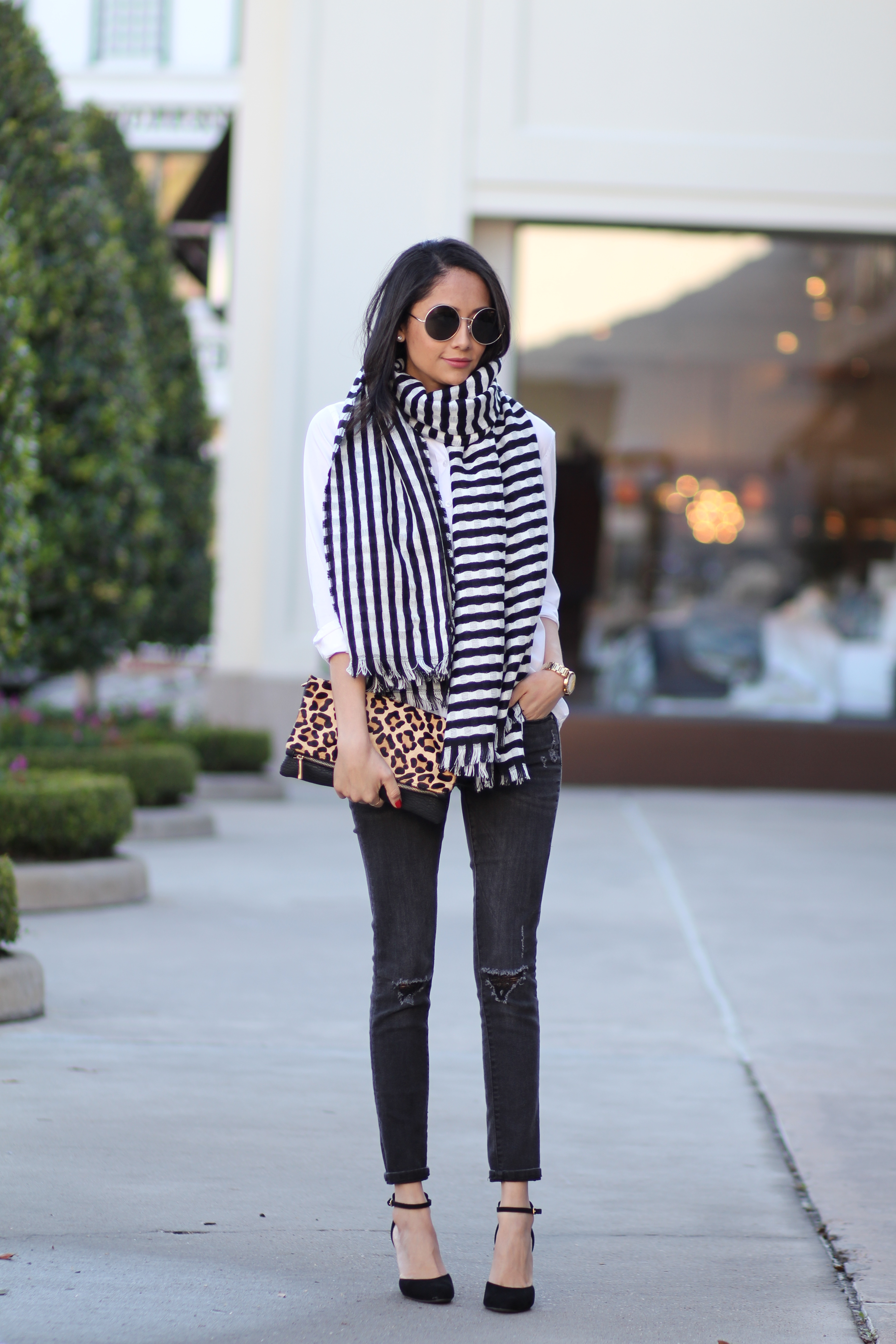 Lifestyle blogger Lilly Beltran of Daily Craving wearing a chic fall outfit with a striped scarf and leopard print clutch