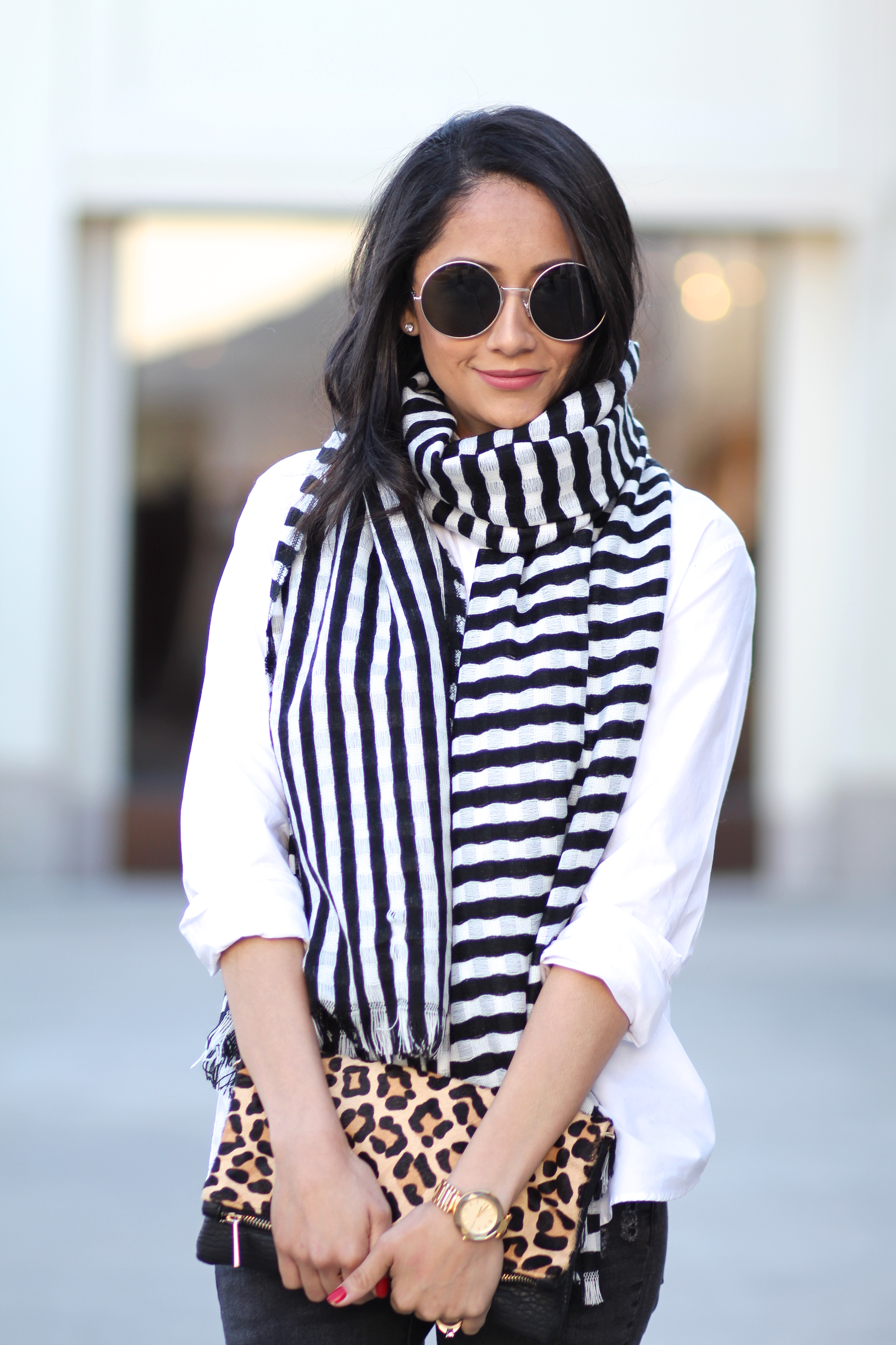 Lifestyle blogger Lilly Beltran wearing a striped scarf and round sunglasses