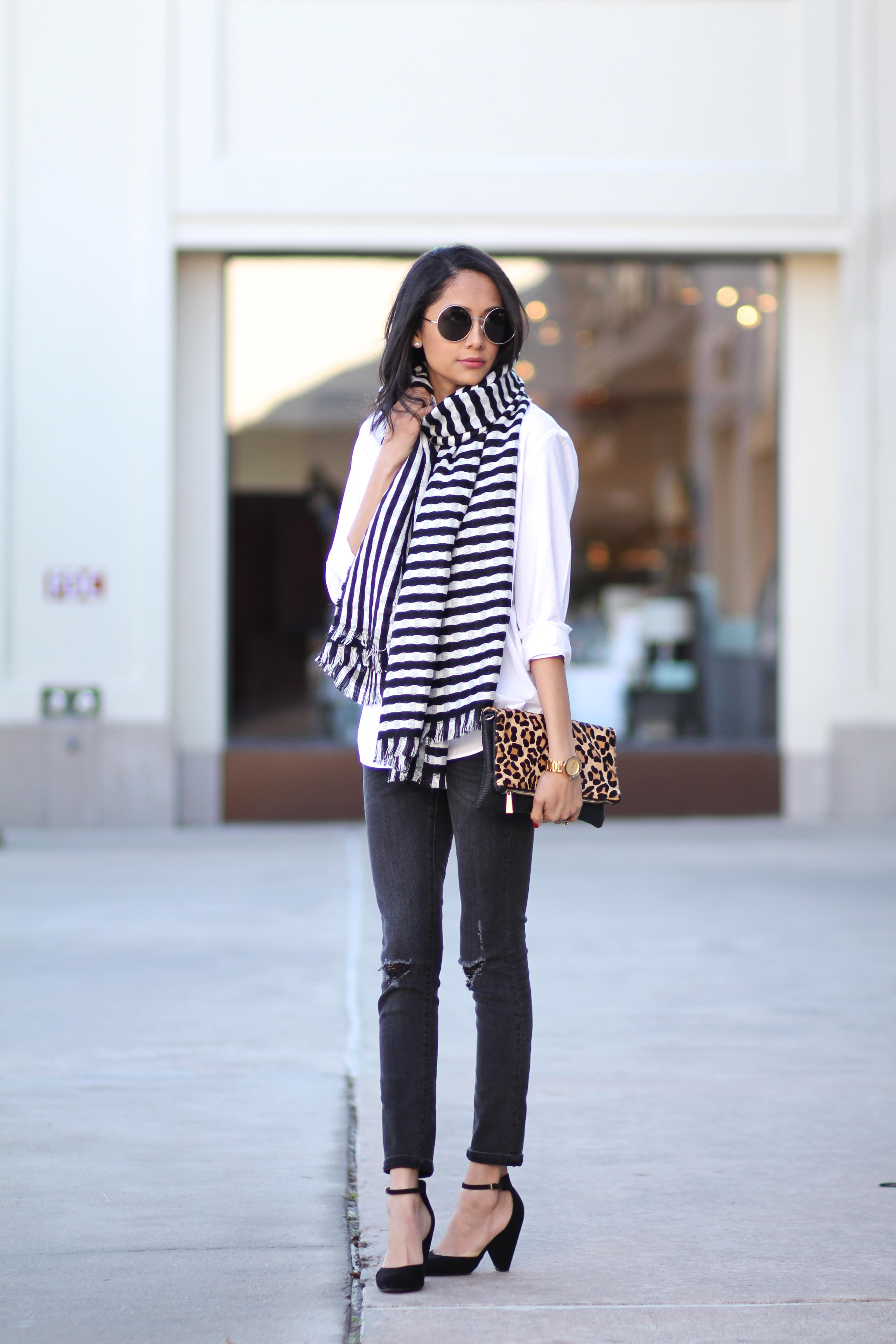 Lilly Beltran of Daily Craving in a fall outfit with black skinny jeans and round sunglasses