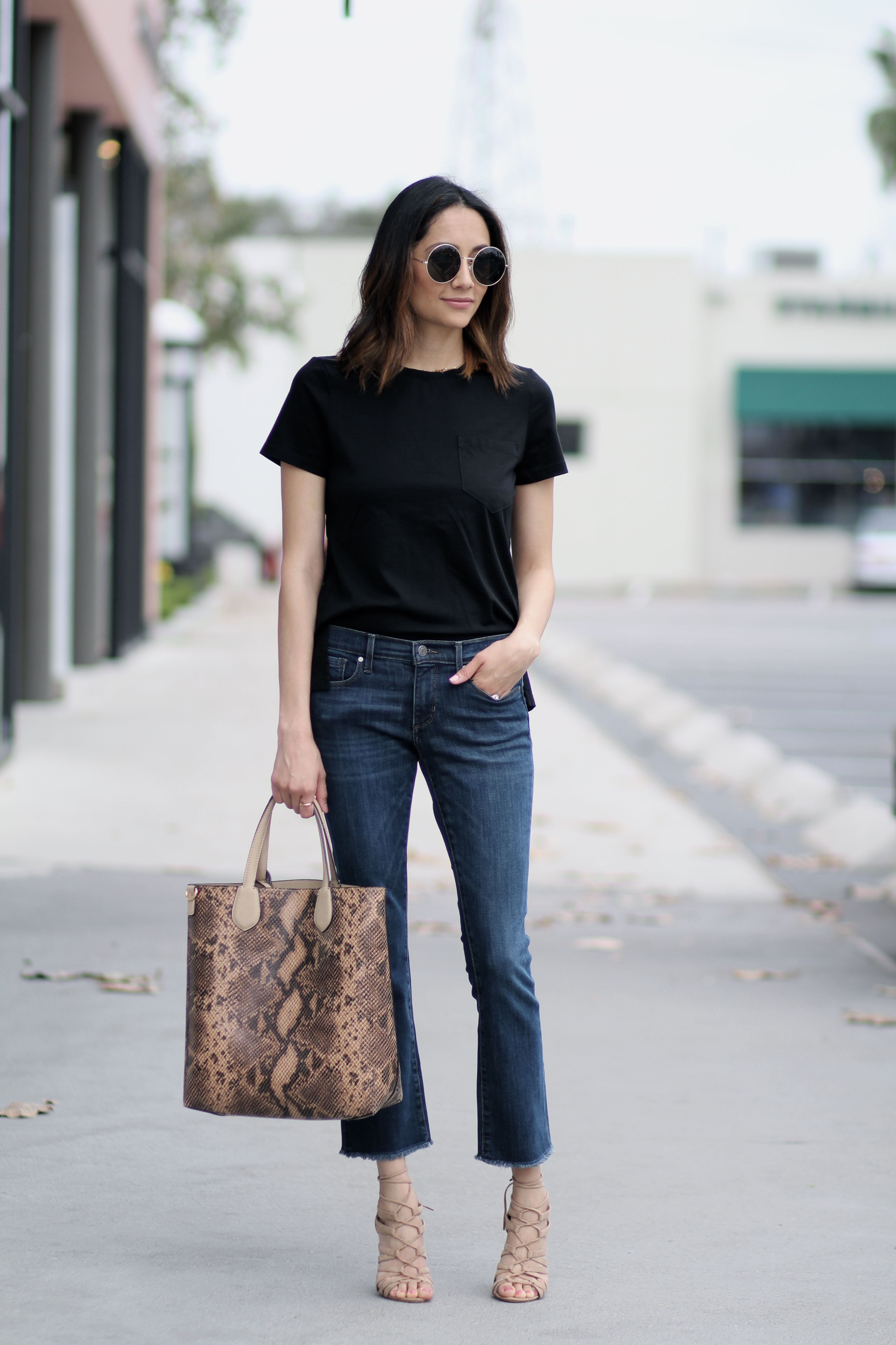 Lifestyle blogger Lilly Beltran of Daily Craving in flare jeans and round sunglasses