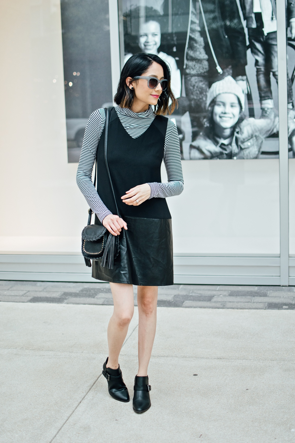 Style blogger Daily Craving in a layered fall outfit with a black dress and striped long sleeve top and ankle boots