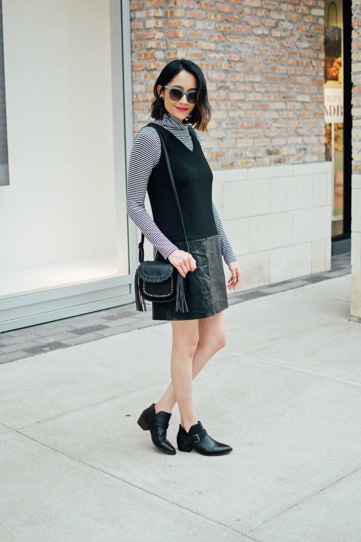 Lilly Beltran of Daily Craving in a chic fall look with a black dress striped top and black ankle boots