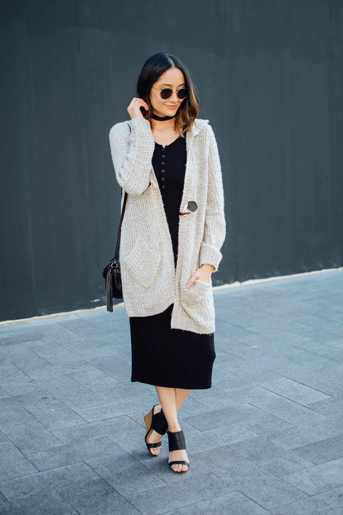 Lilly Beltran of Daily Craving wearing a fall appropriate look with a black knit dress and hooded cardigan