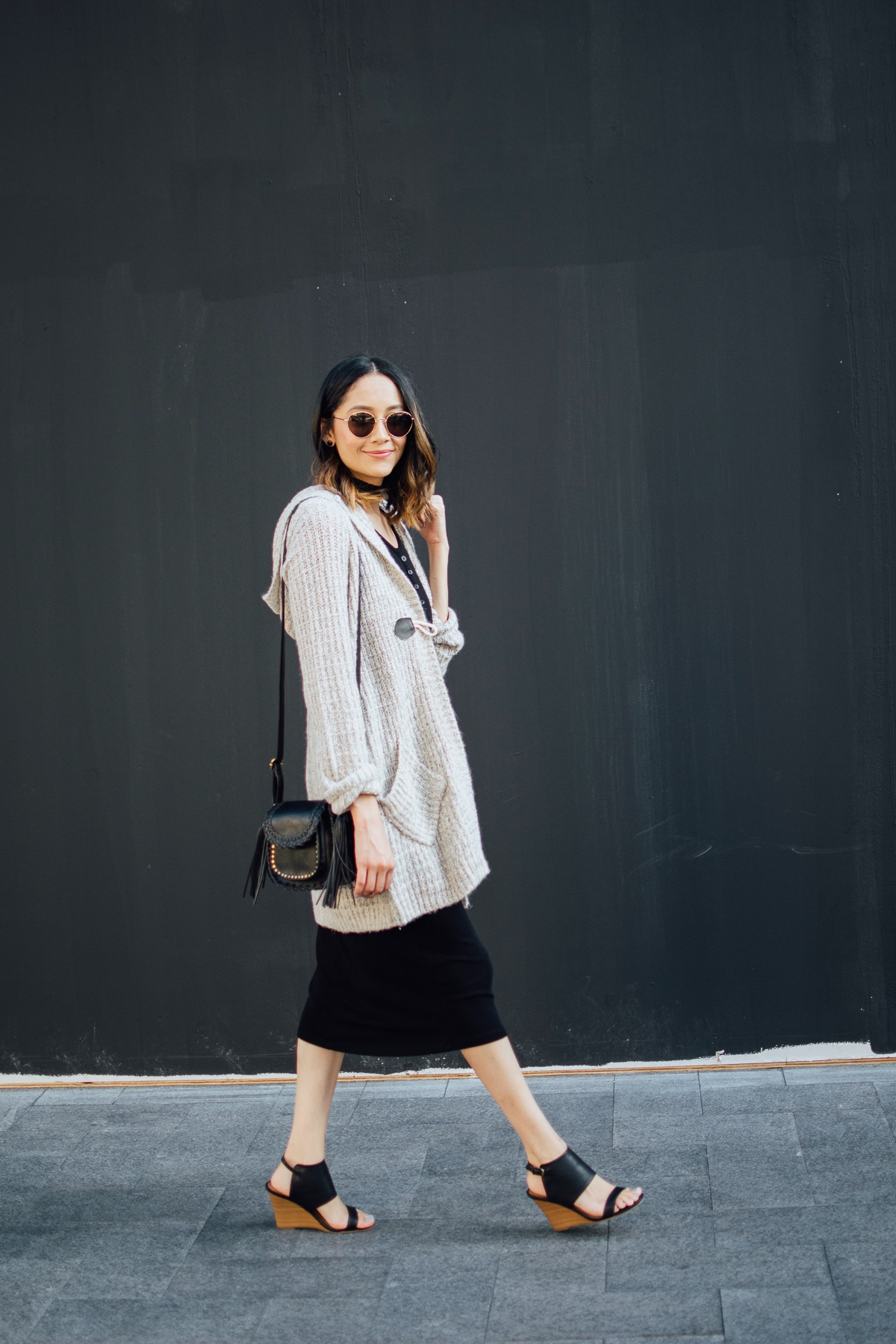 Daily Craving wearing a cozy midi cardigan with a black midi dress and wedge sandals