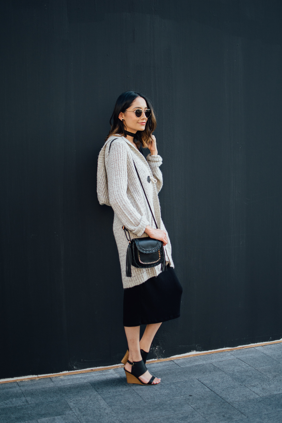 Lilly Beltran of Daily Craving wearing a black knit dress with a midi length hooded cardigan