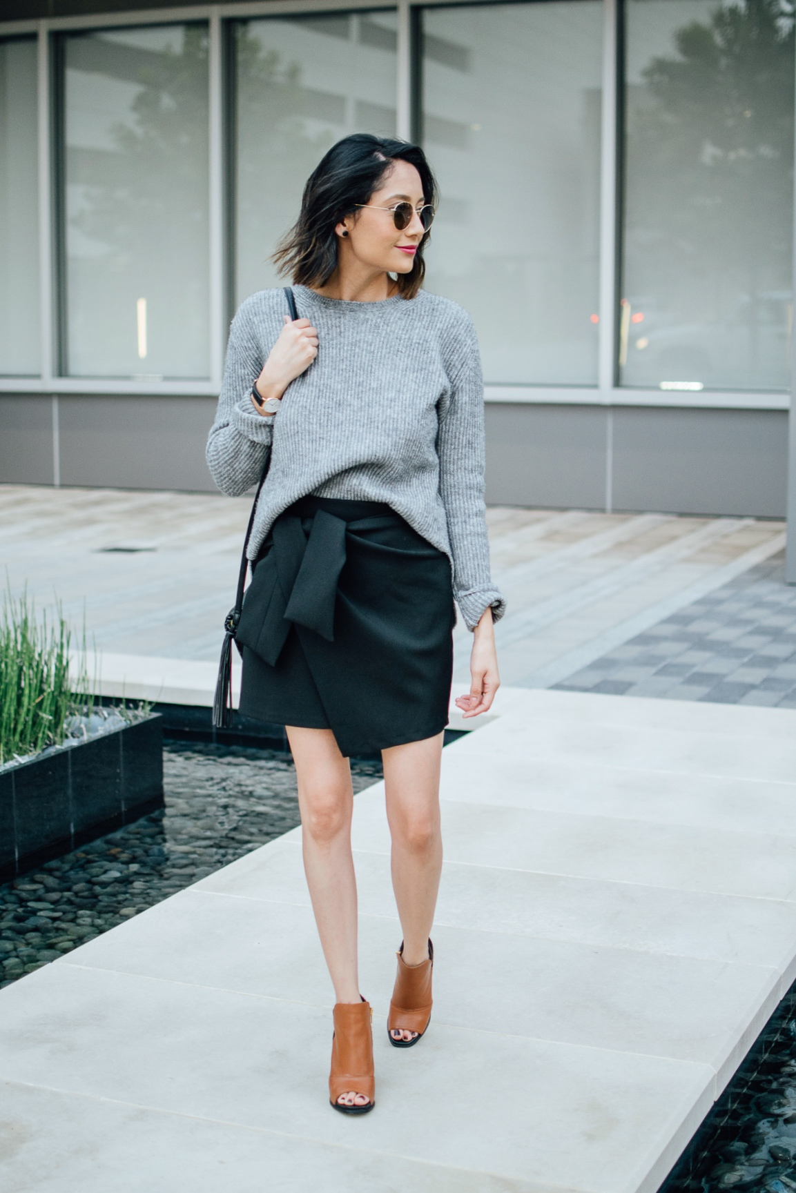 Lilly Beltran of Daily Craving blog in a chic fall outfit with a grey sweater, black wrap skirt and leather boots