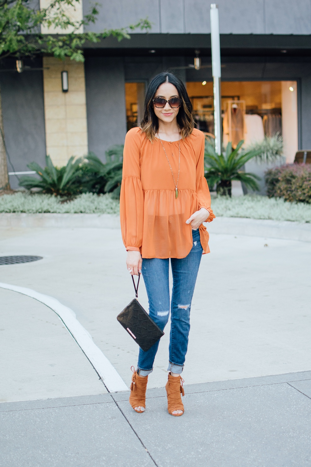 Fashion blogger Lilly Beltran of Daily Craving wearing orange lace up sandals and blue denim skinny jeans