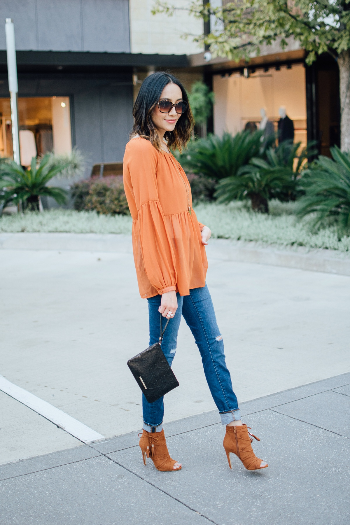 Fashion blogger Lilly Beltran of Daily Craving in a casual fall look in an orange top and black Elaine Turner Clutch