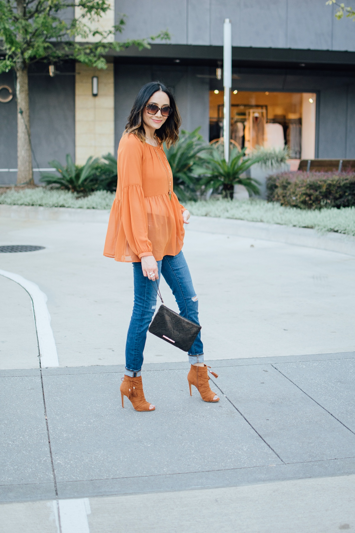 Lilly Beltran of Daily Craving in a long sleeve orange top and squared sunglasses