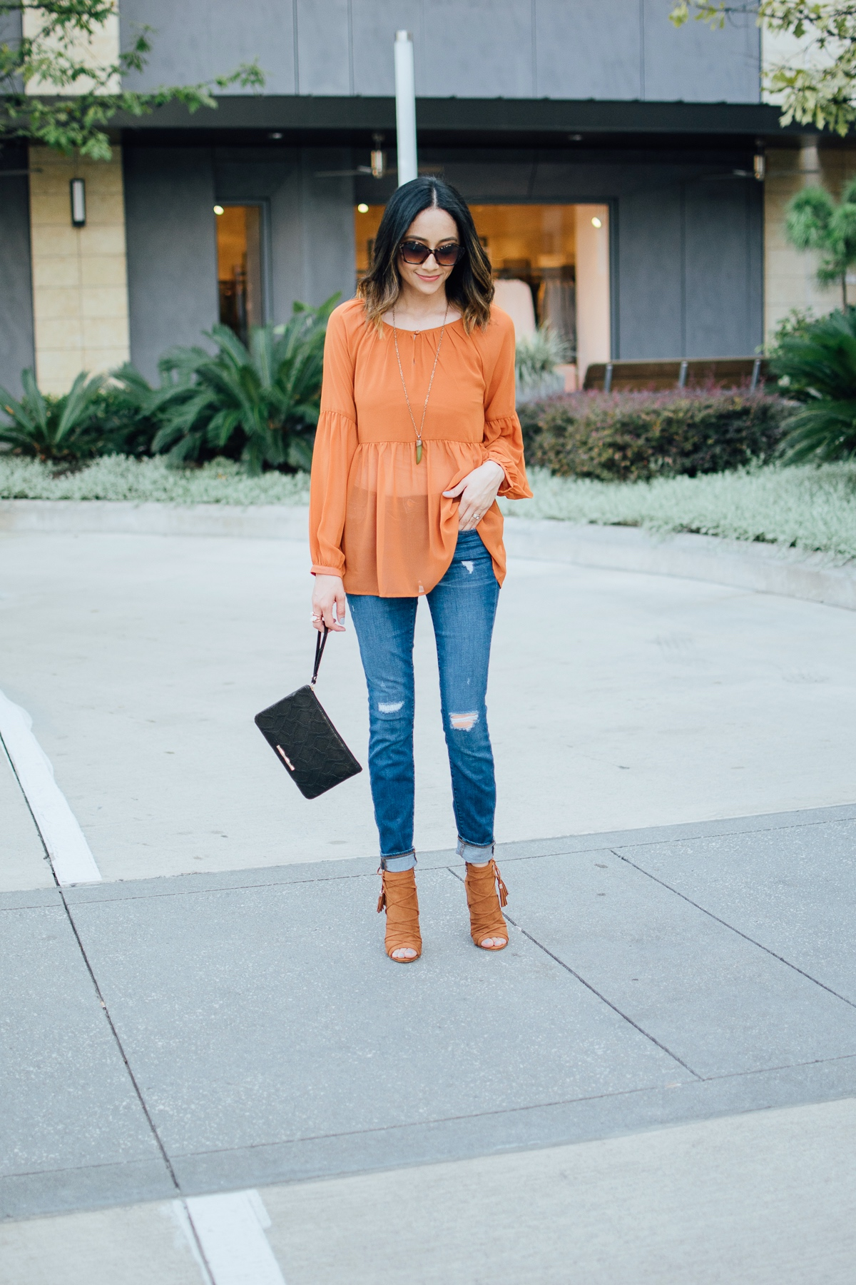 Lilly Beltran of Daily Craving in a fall look wearing an orange top and orange lace up sandals