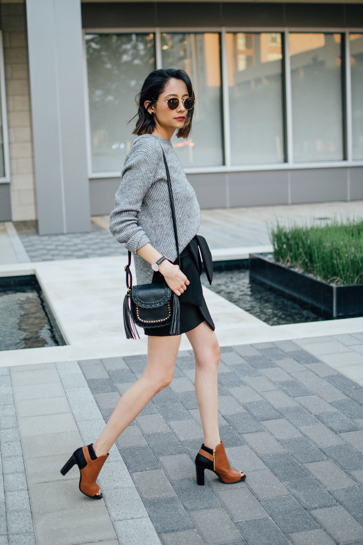 Daily Craving wearing a trendy fall look with an oversized grey sweater, black mini skirt and brown leather boots