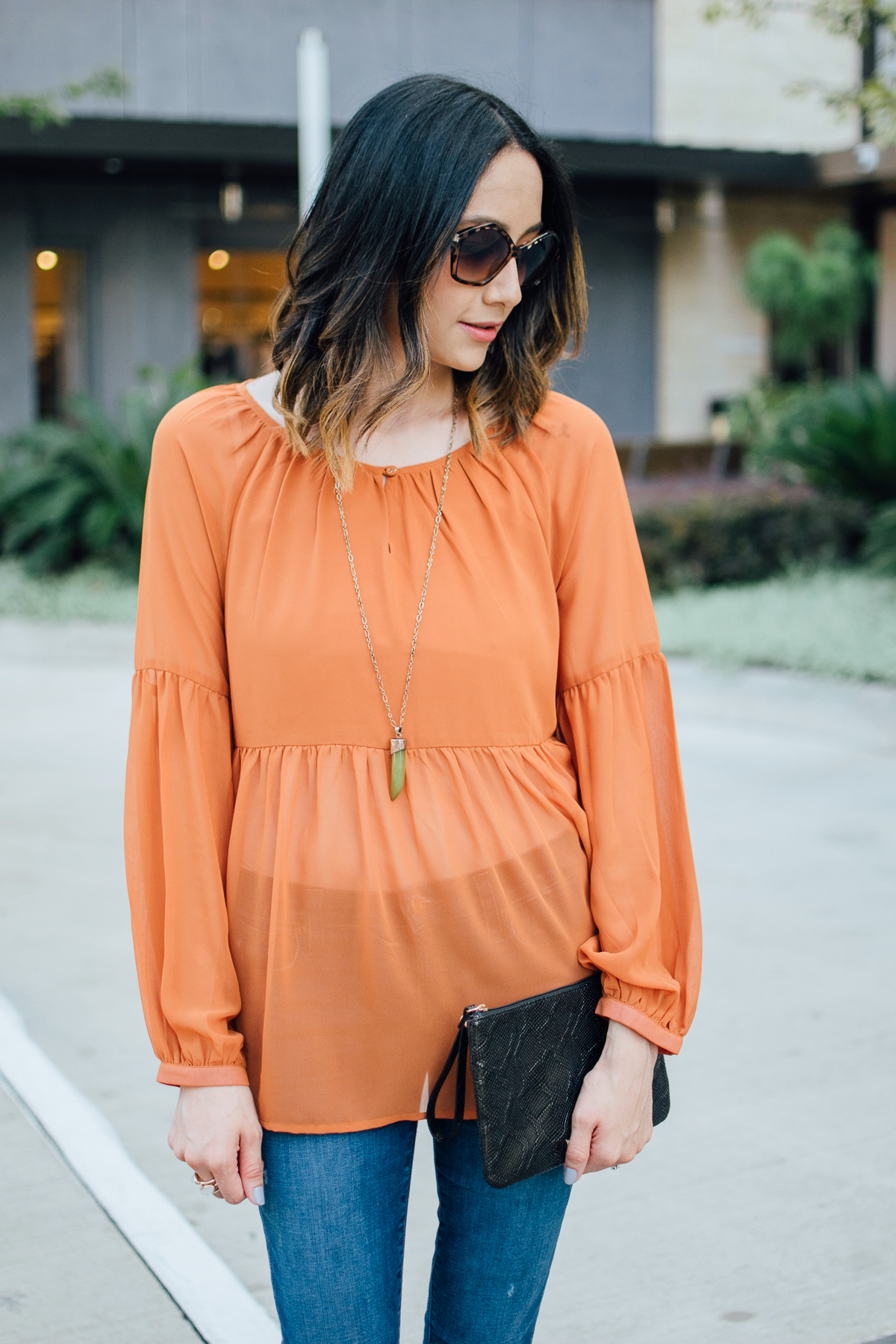Lilly Beltran of Daily Craving fashion blog in a long sleeve orange top and black Elaine Turner clutch