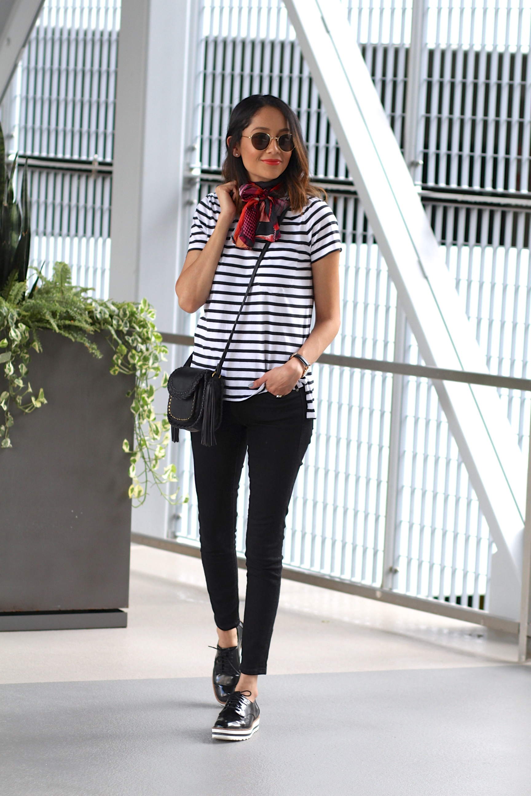 Lifestyle blogger Lilly Beltran in a casual look wearing black skinny jeans and a striped tee