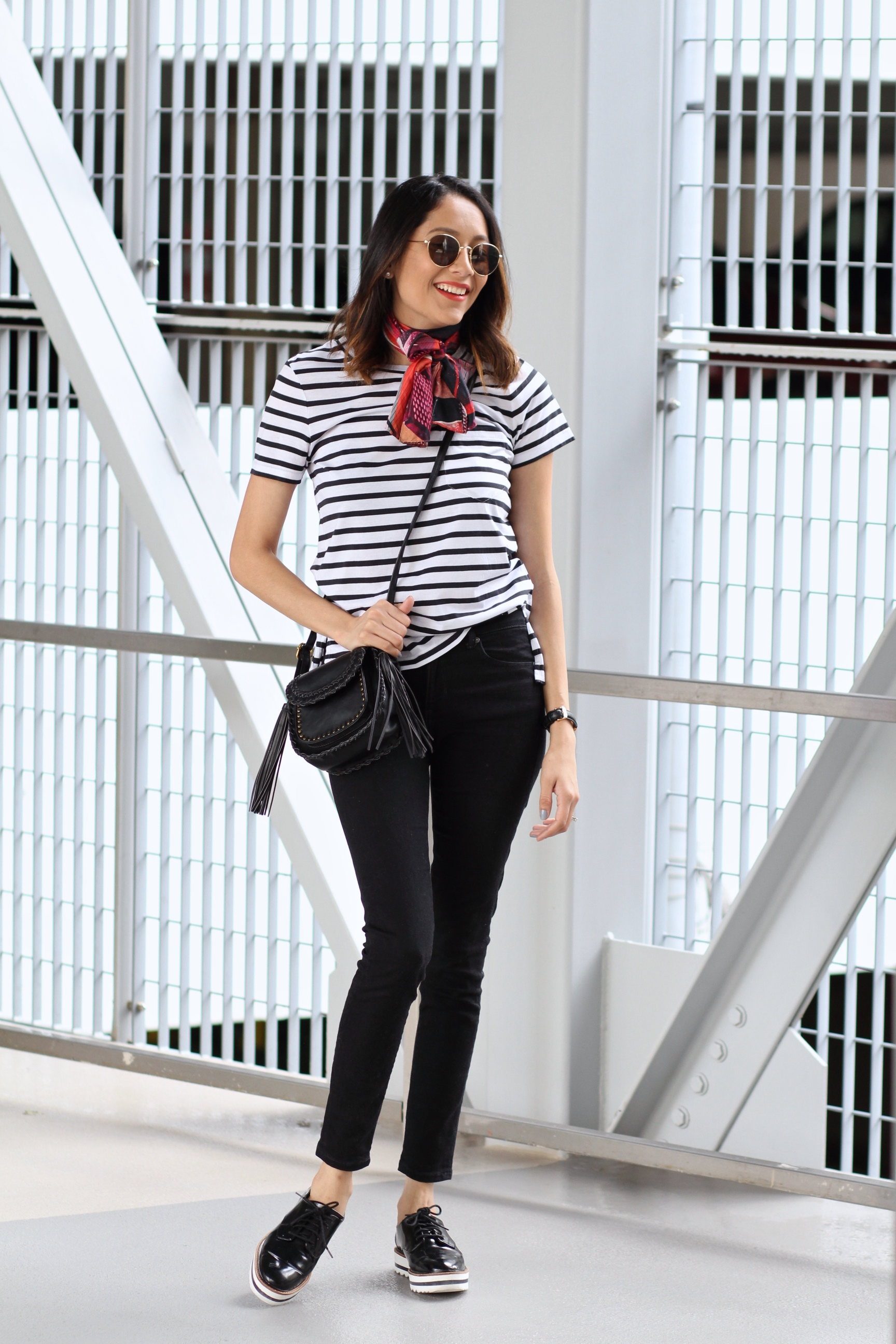 Lilly Beltran from Daily Craving wearing black skinny jeans and round sunglasses
