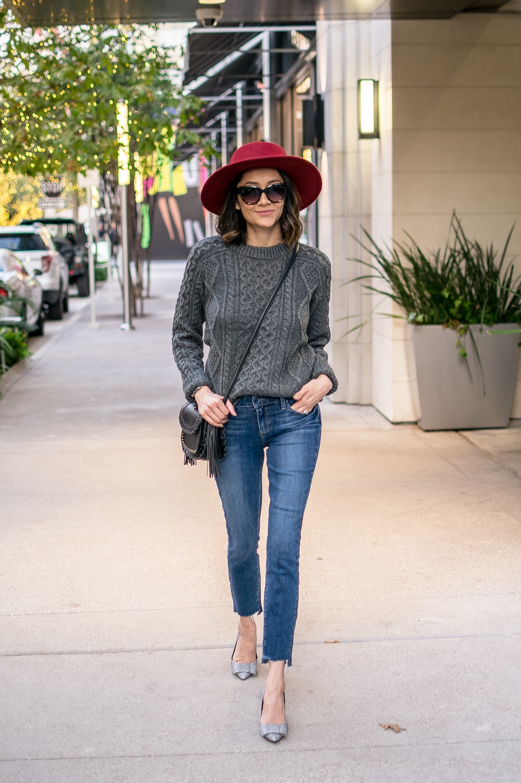 Lilly Beltran of Daily Craving blog wearing a cozy Thanksgiving look with raw hem jeans and glitter bow heels
