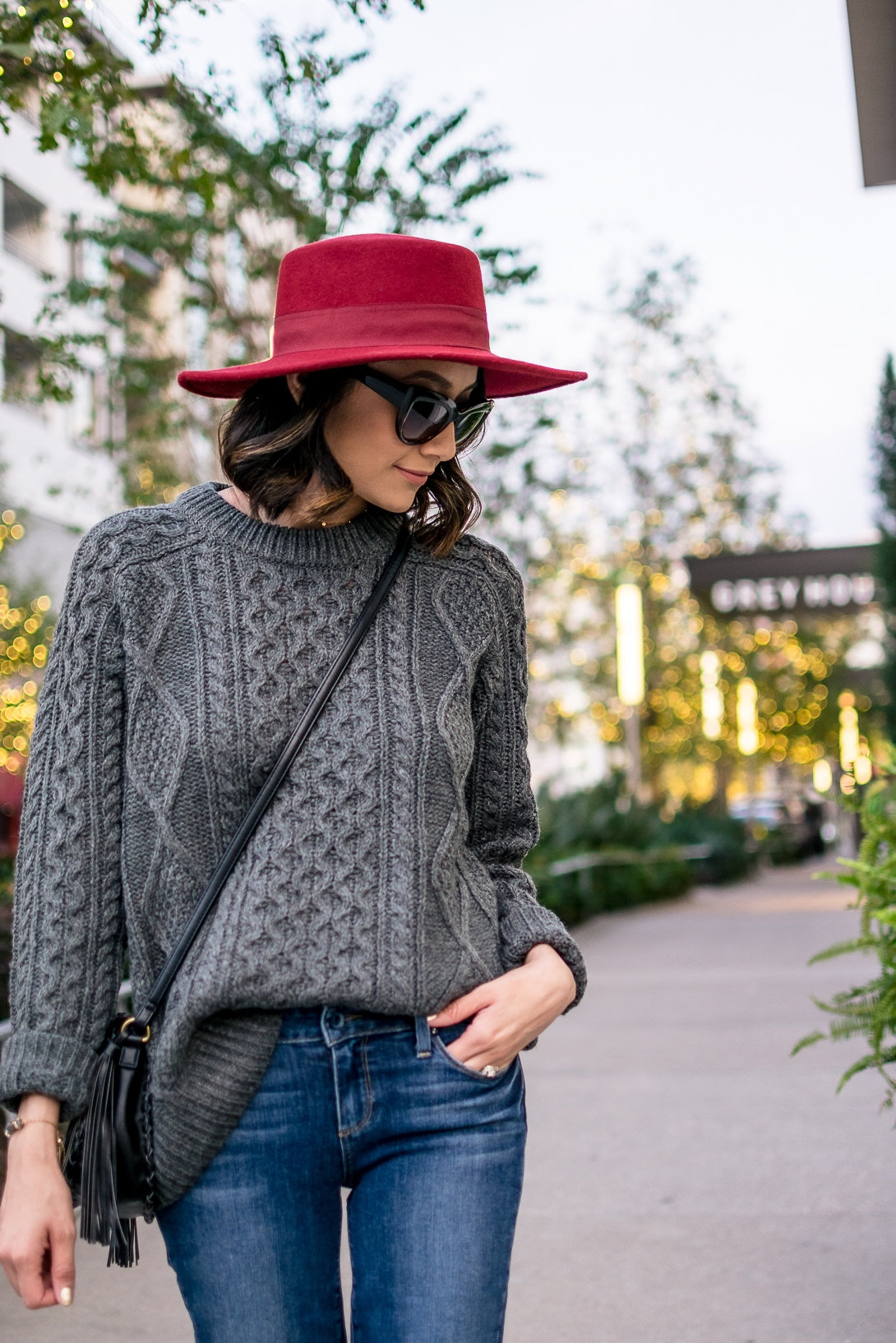 Daily Craving wearing a red hat with a grey cable knit sweater