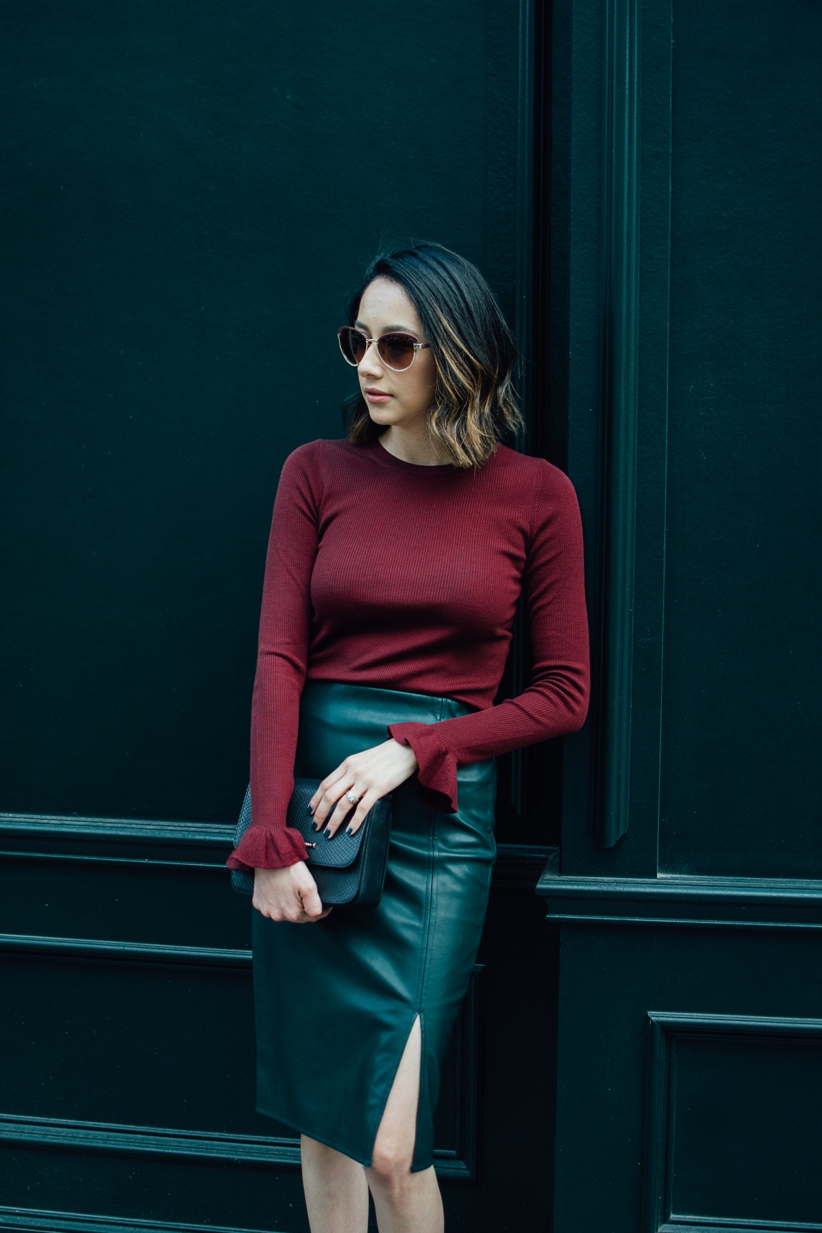 Style blogger Daily Craving wearing vegan leather skirt with a Burgundy bell sleeve sweater