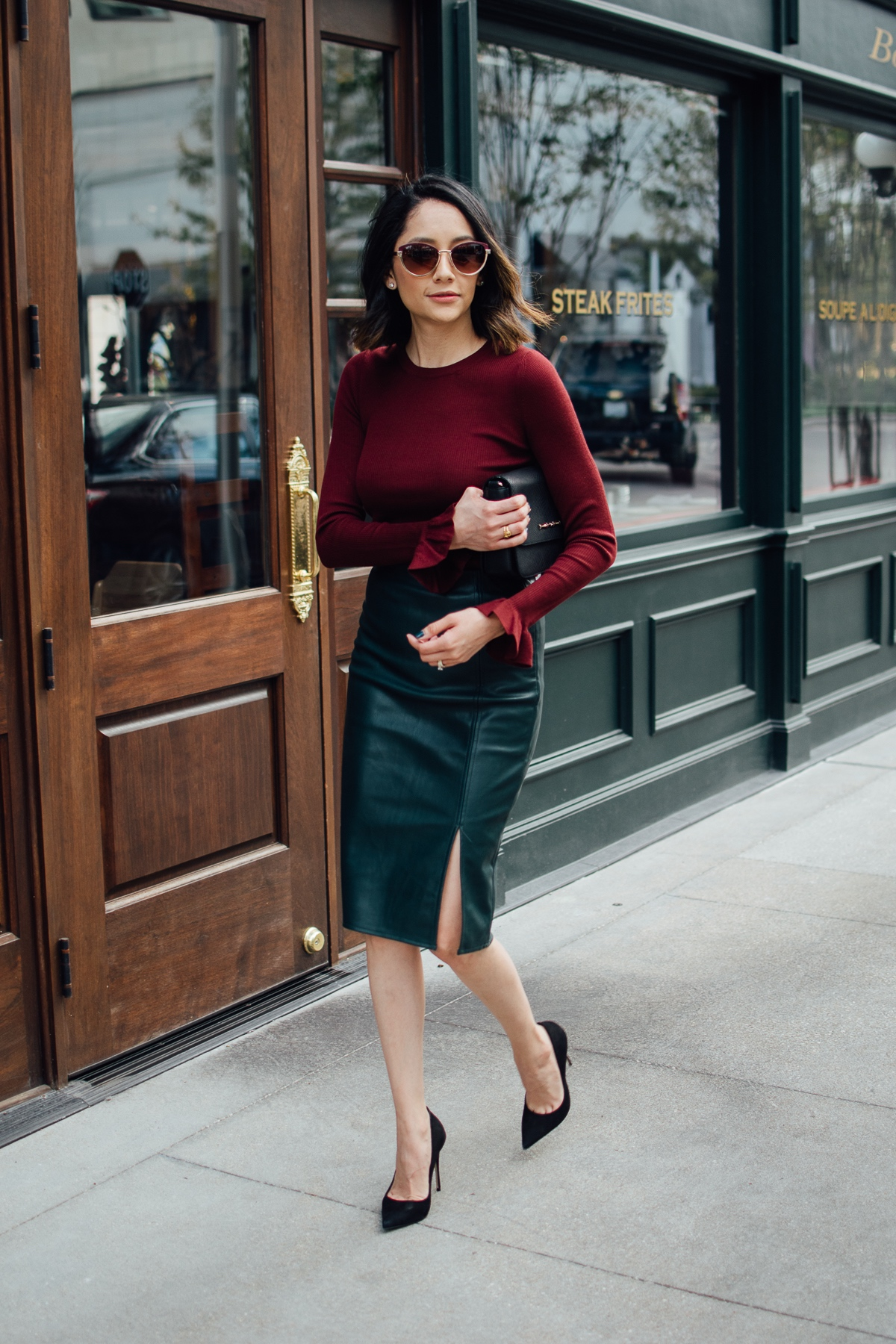 Houston style blogger Daily Craving wearing a holiday ready look with a green leather skirt, black pumps, and Burgundy sweater