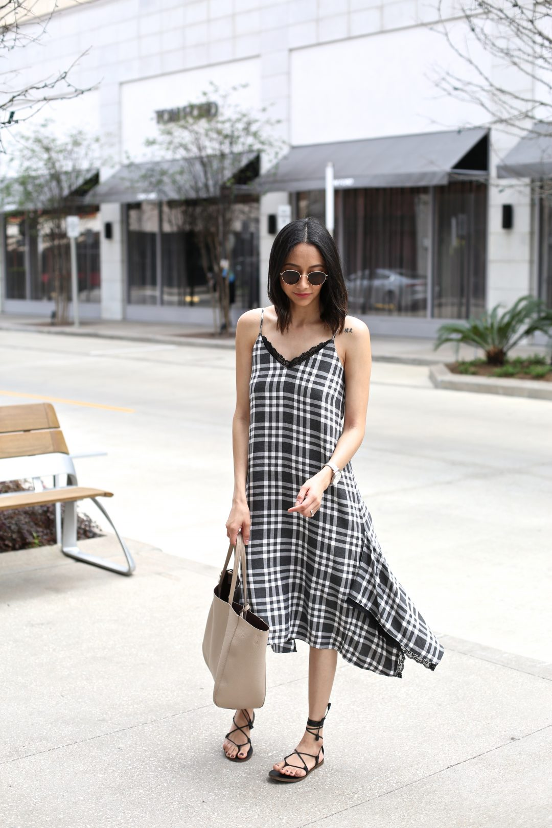 Style blogger Lilly Beltran wearing a casual look in a black plaid dress and lace-up sandals