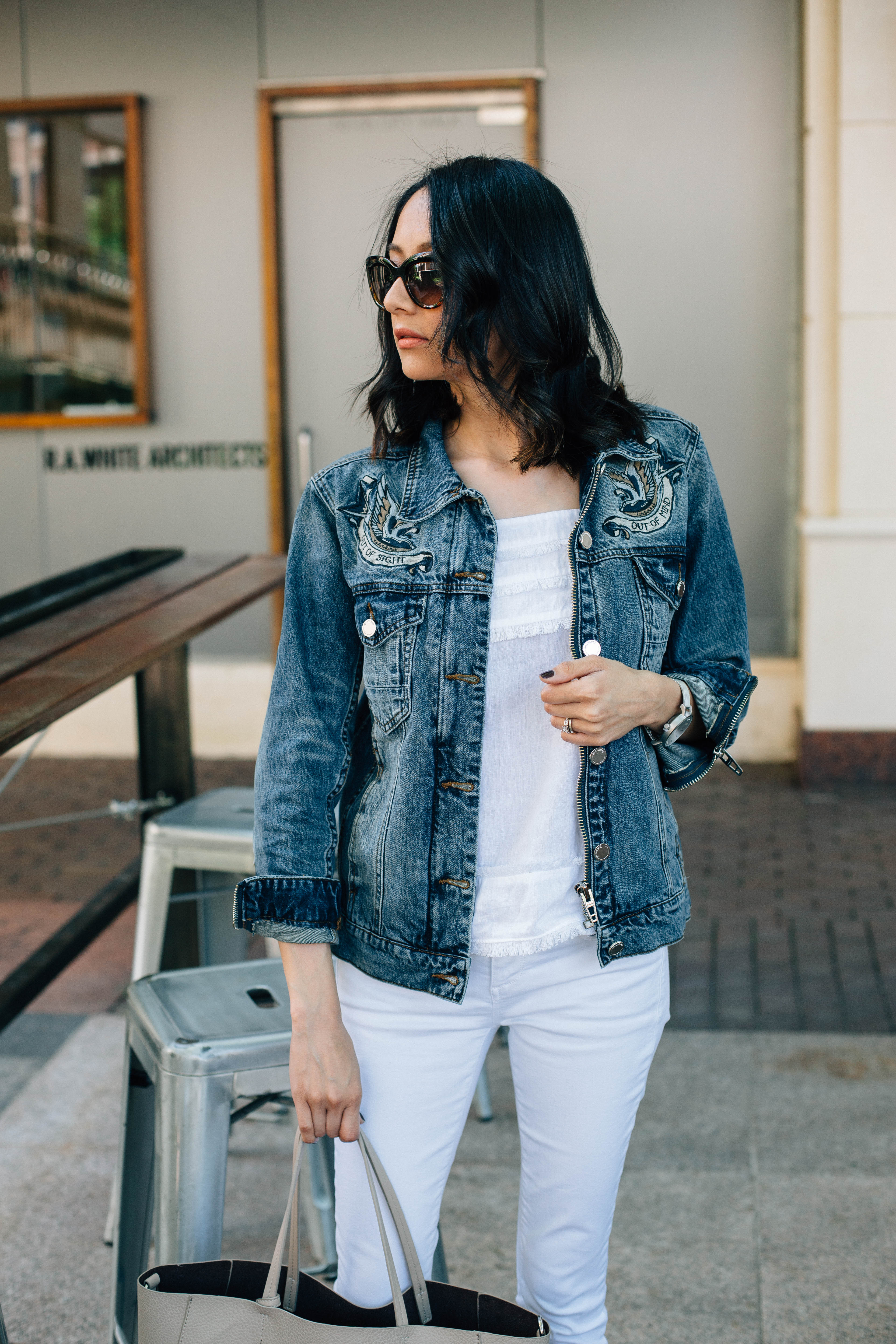Lifestyle blogger Lilly Beltran of Daily Craving in a casual weekend look wearing an embroidered denim jacket and white skinny jeans