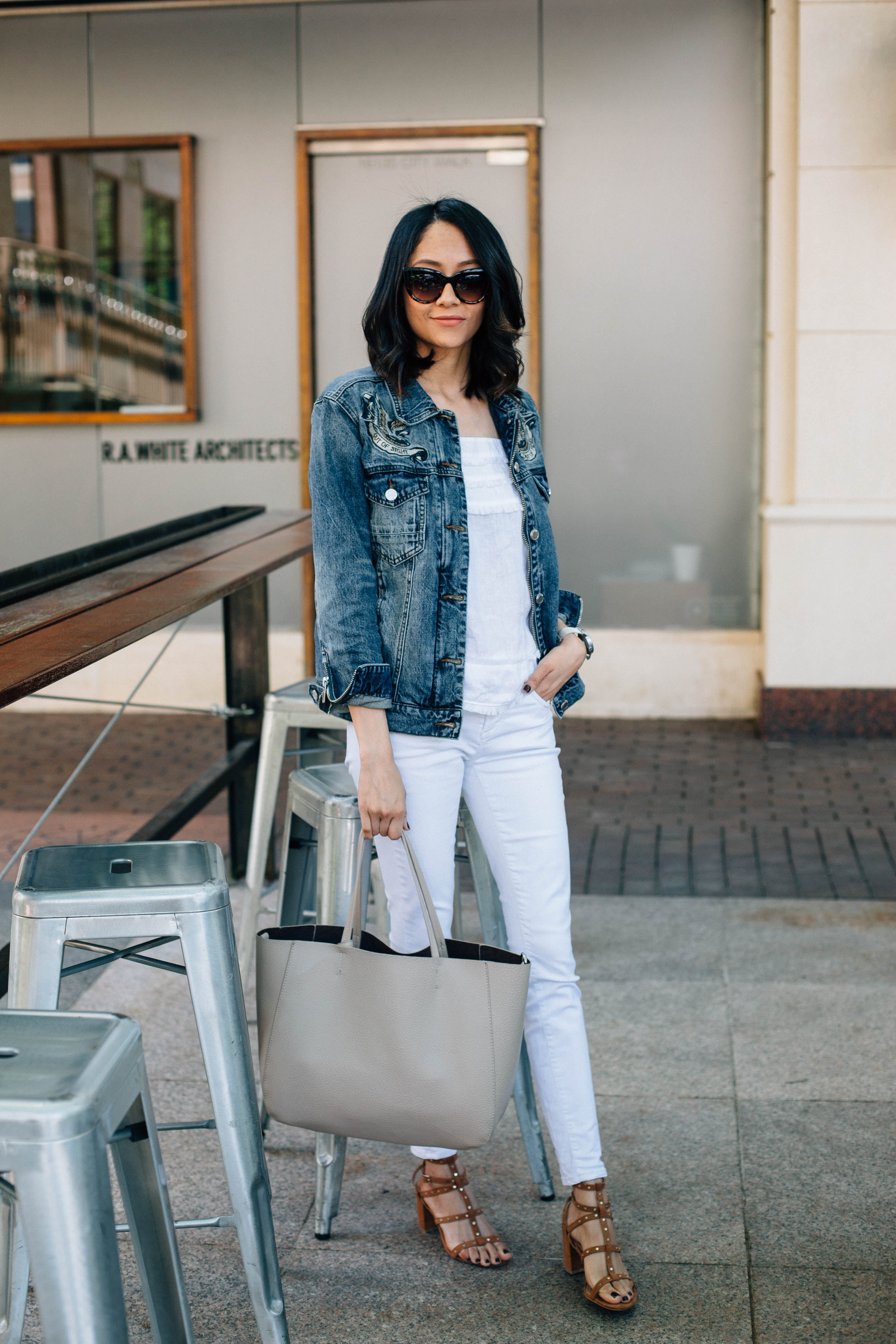 Lifestyle blogger Lilly Beltran of Daily Craving wearing a denim on denim look with an oversized denim jacket and studded sandals