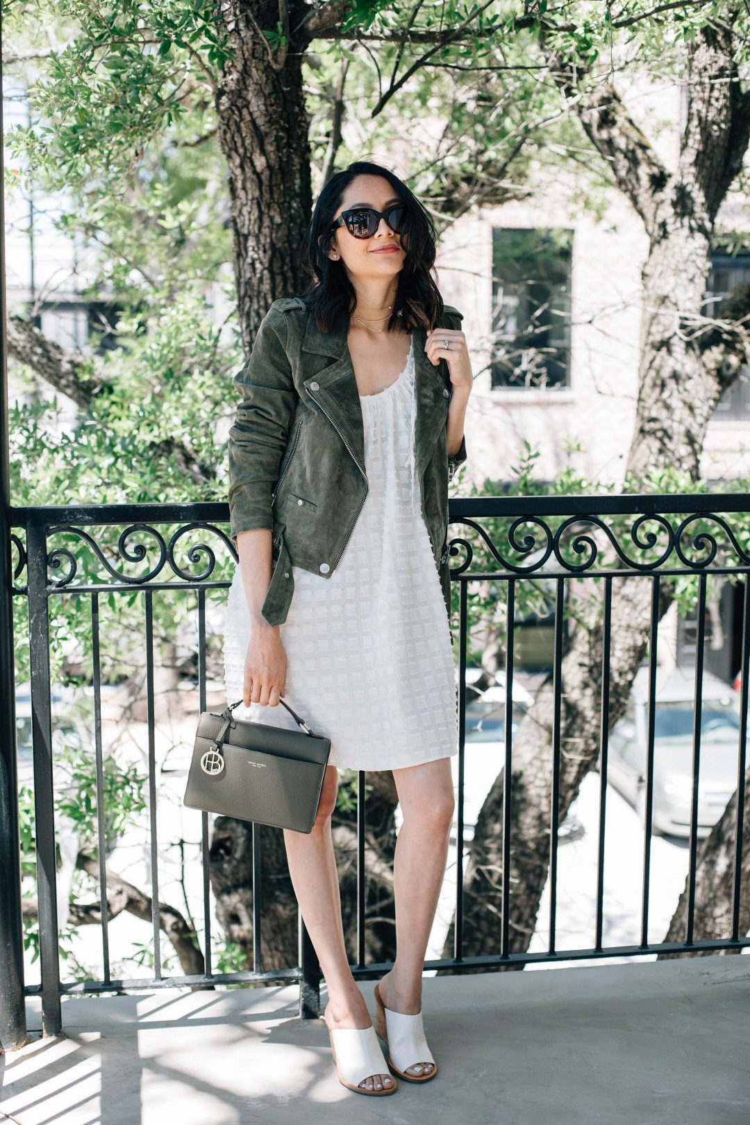 Lilly Beltran of Daily Craving in a suede moto jacket and summer dress