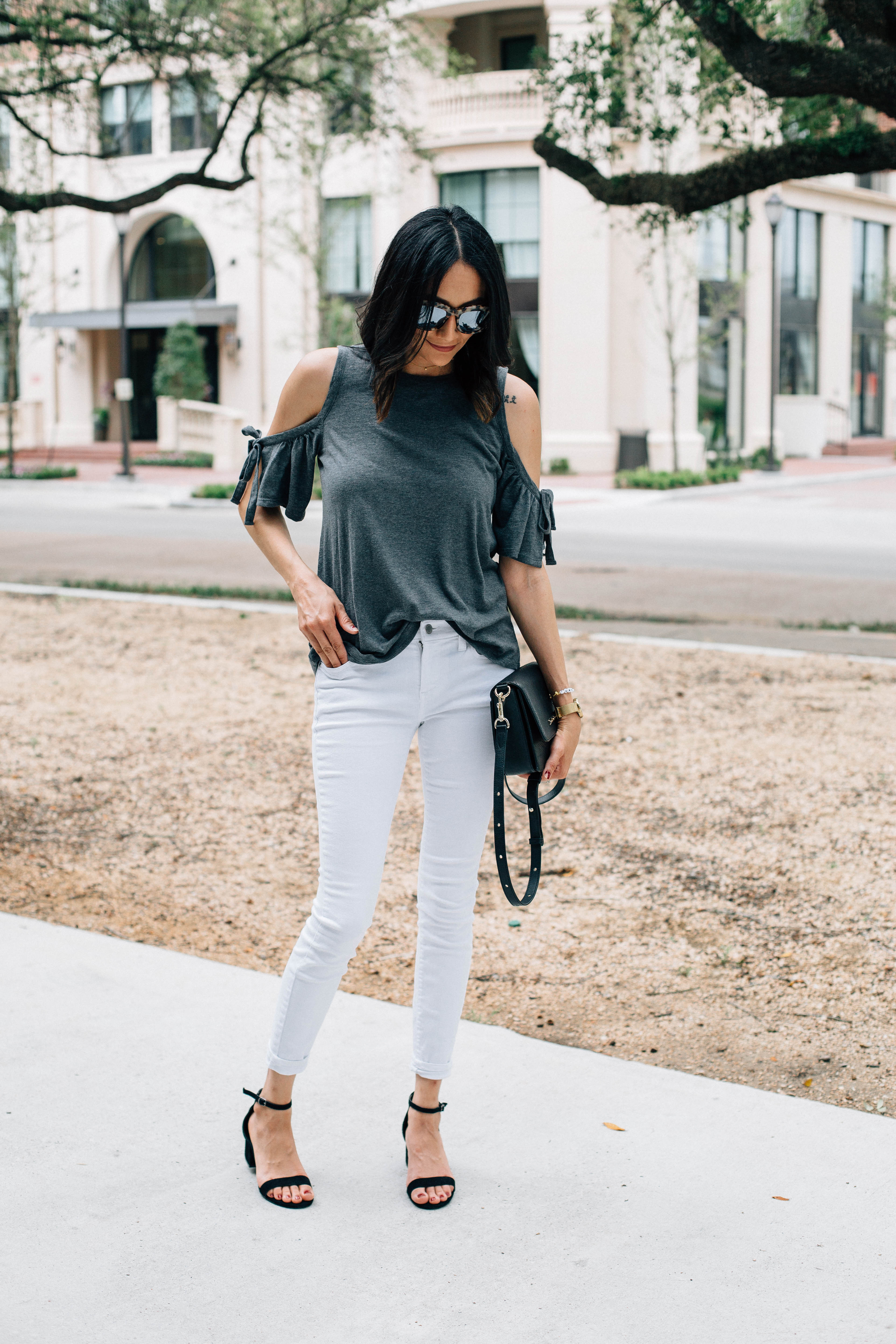 Lifestyle blogger Lilly Beltran of Daily Craving in a grey cold shoulder top and white jeans