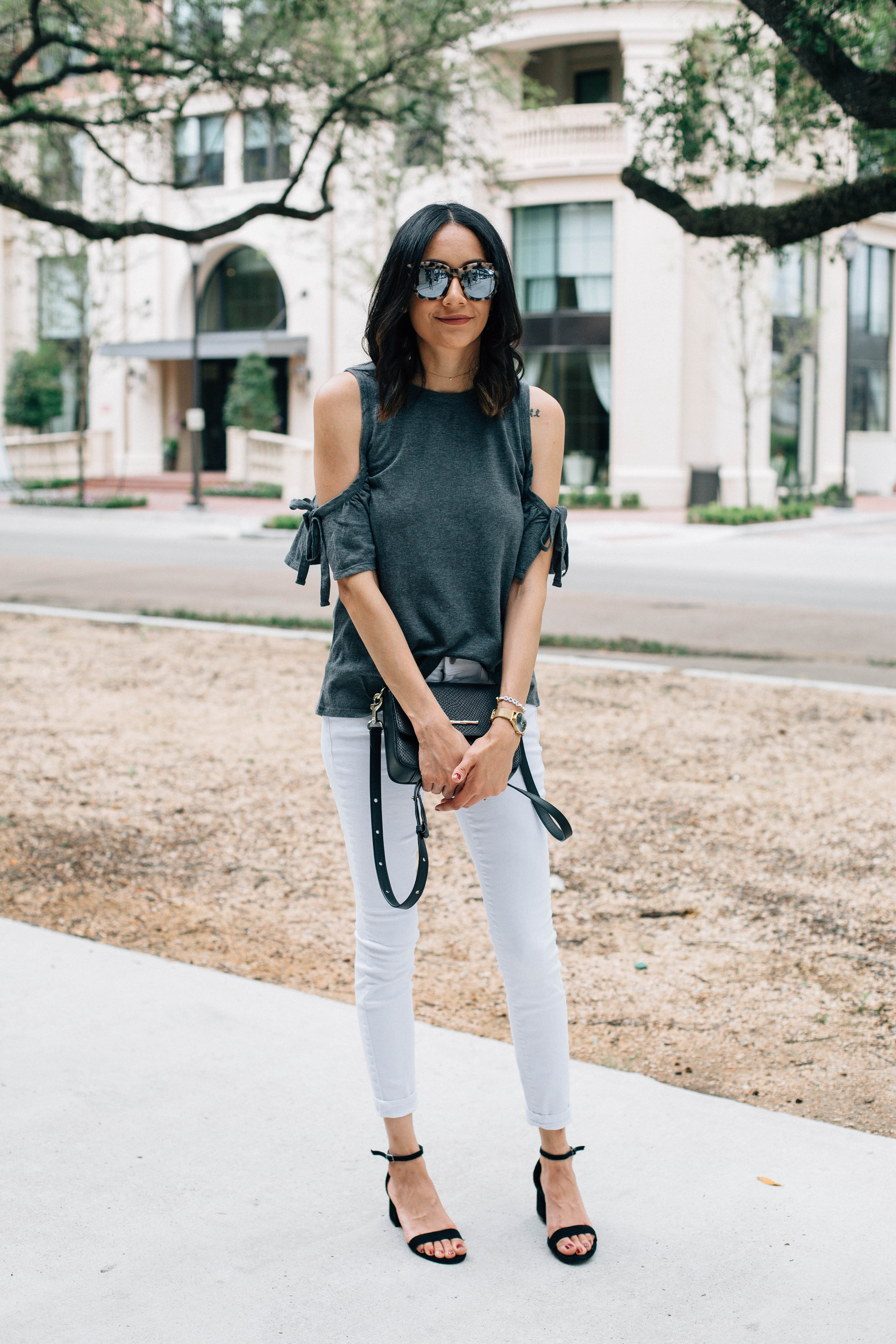 Lifestyle blogger Lilly Beltran of Daily Craving in a casual look in a grey cold shoulder top & white skinny jeans