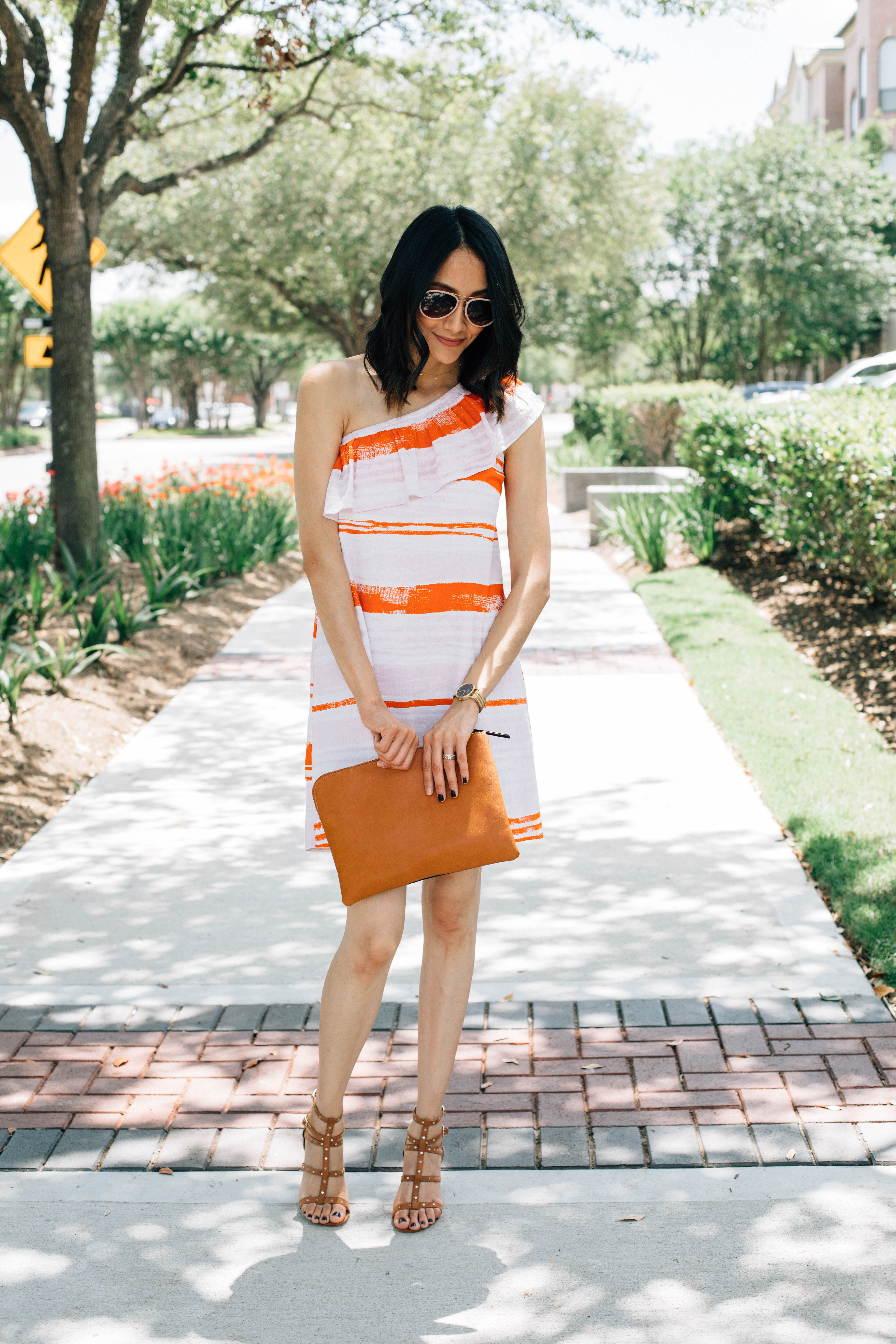Lilly Beltran of Daily Craving blog in a chic brunch look with a striped one-shoulder dress, studded sandals and who what wear clutch