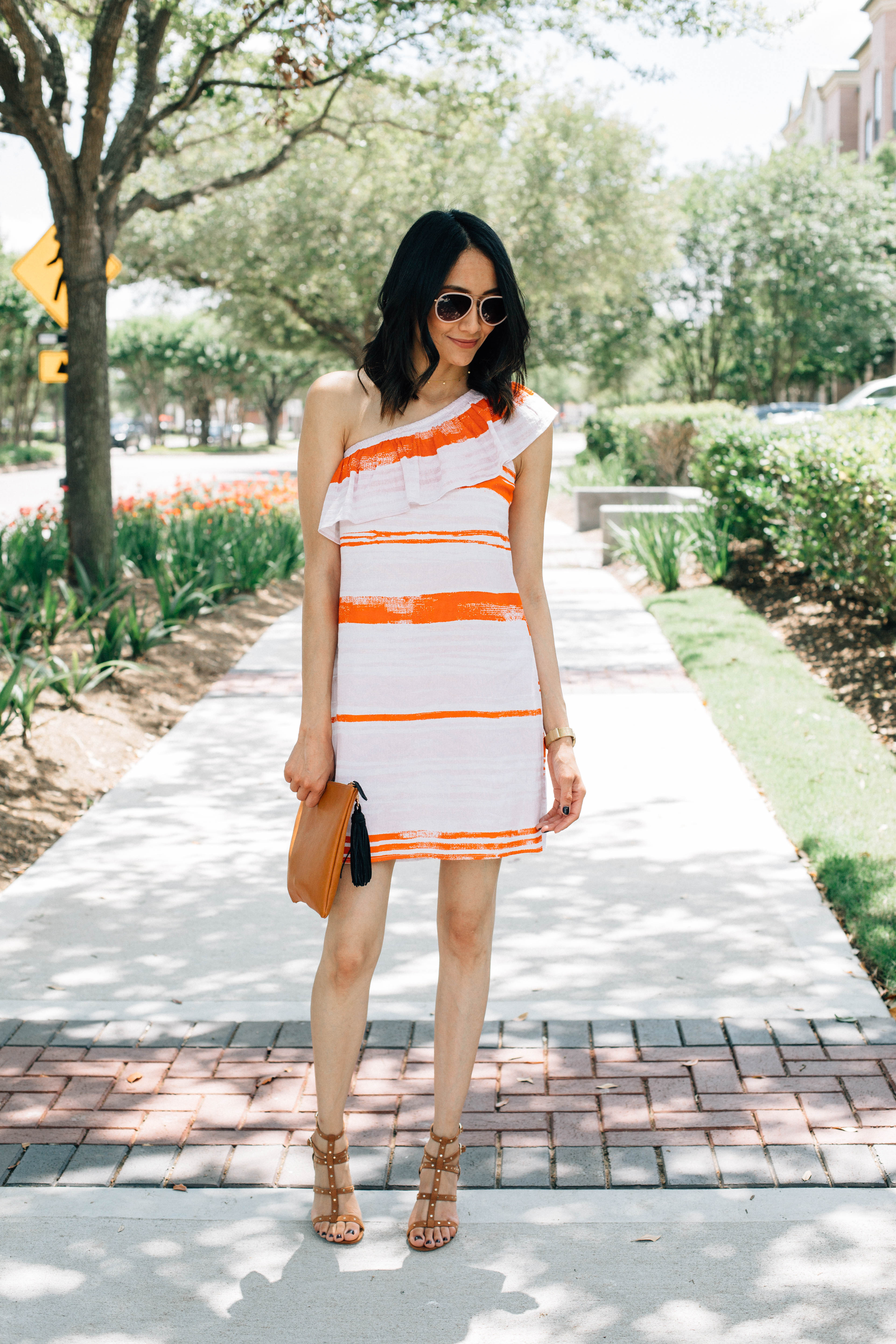 Style blogger Lilly Beltran wearing a striped one-shoulder dress with Valentino Rockstud dupes and who what wear clutch