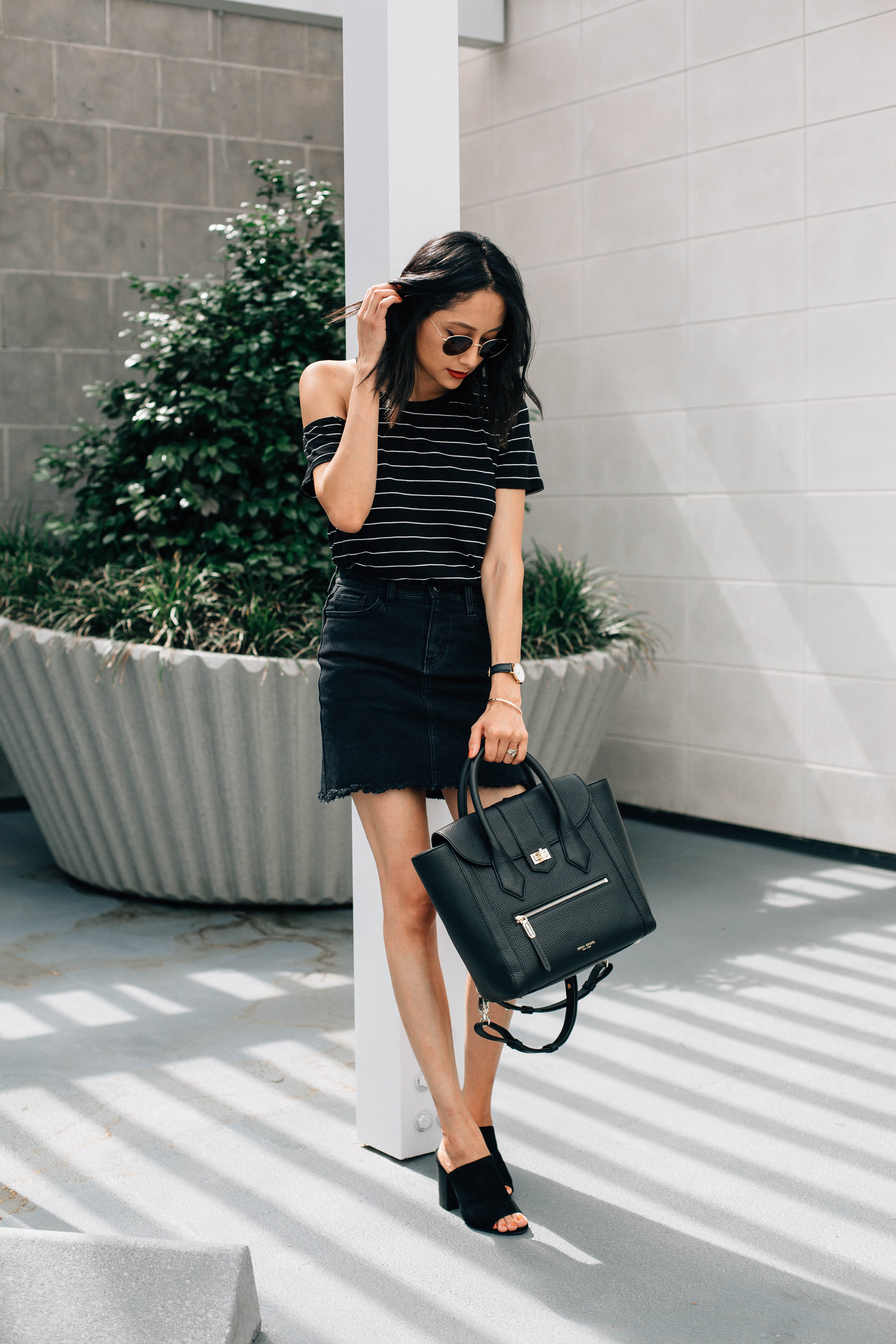 Lifestyle blogger Lilly Beltran wearing and edgy look wit a black denim skirt and striped tee
