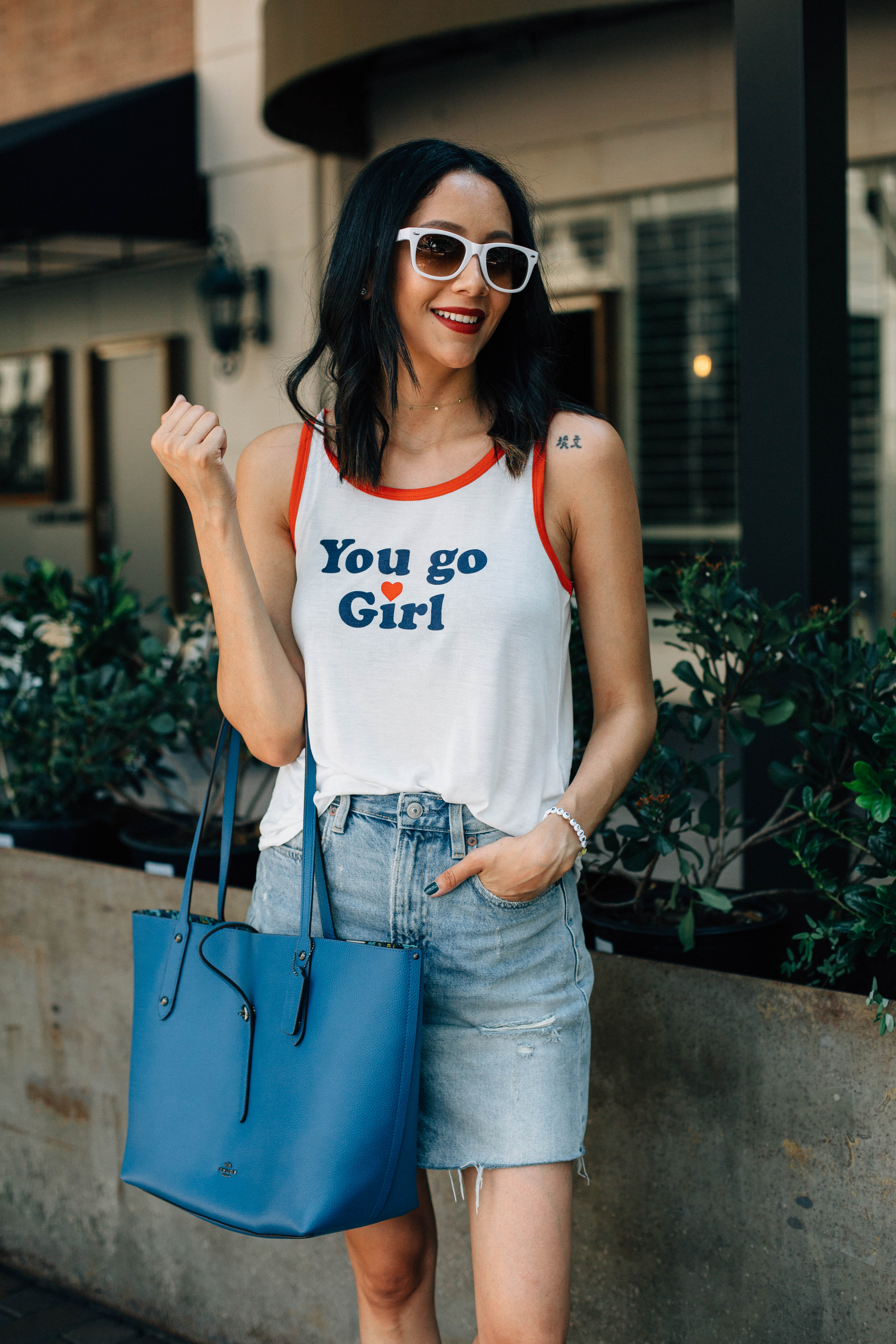 Lifestyle blogger Lilly Beltran from Daily Craving wearing a blue Coach tote