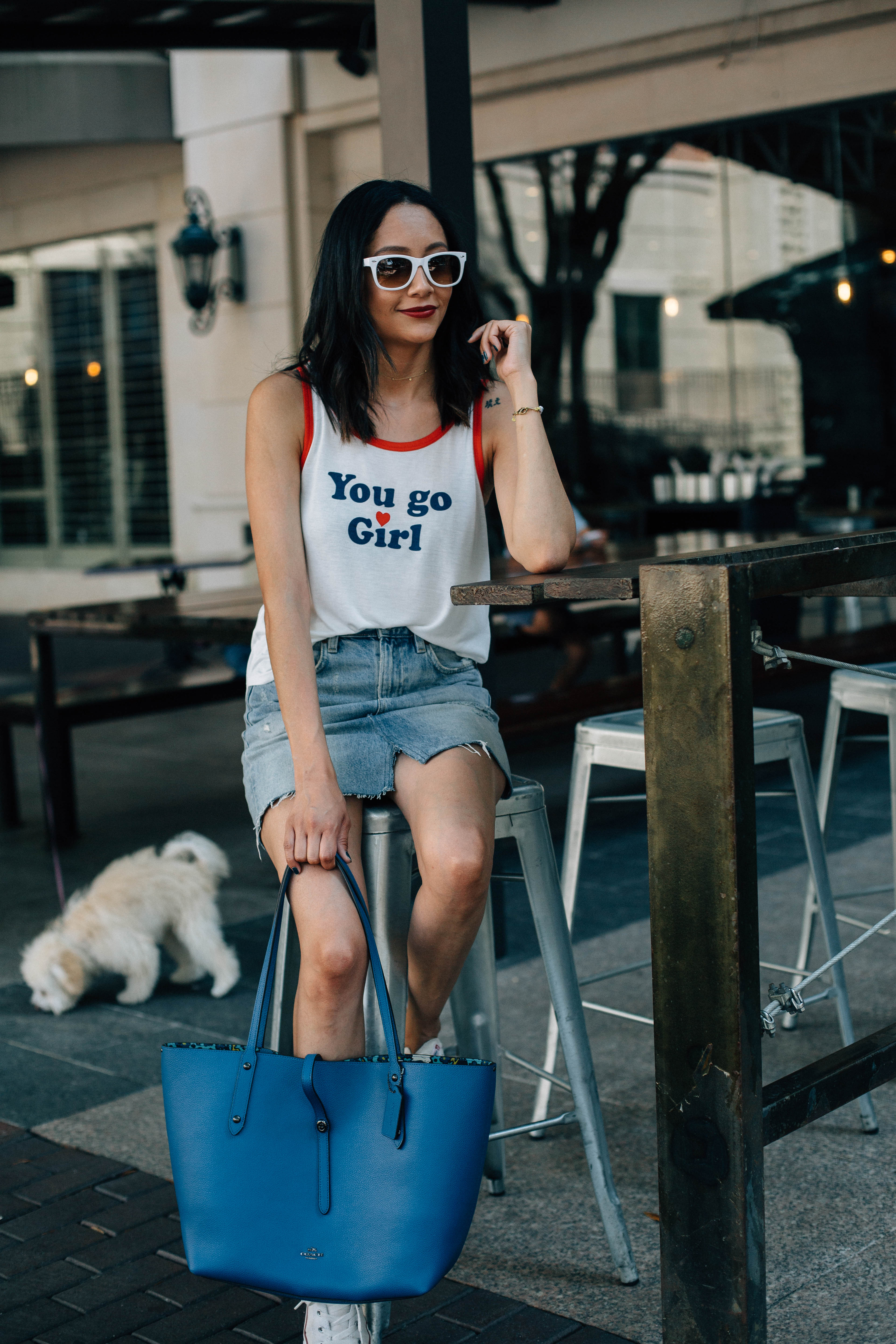 Lifestyle blogger Lilly Beltran of Daily Craving in a casual look wearing a denim skirt and white tee