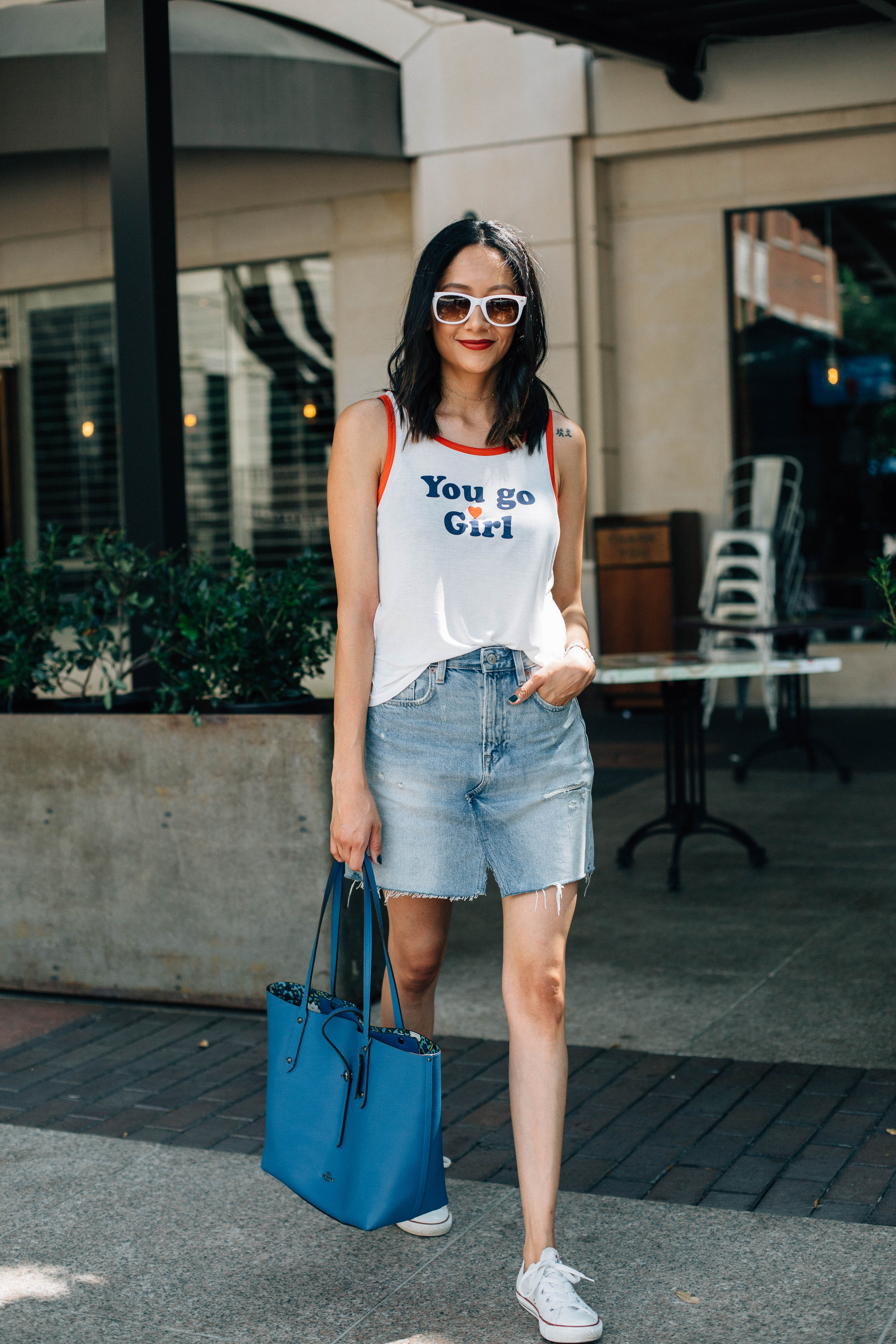 Lifestyle blogger Lilly Beltran of Daily Craving wearing a white printed tee and white sunglasses