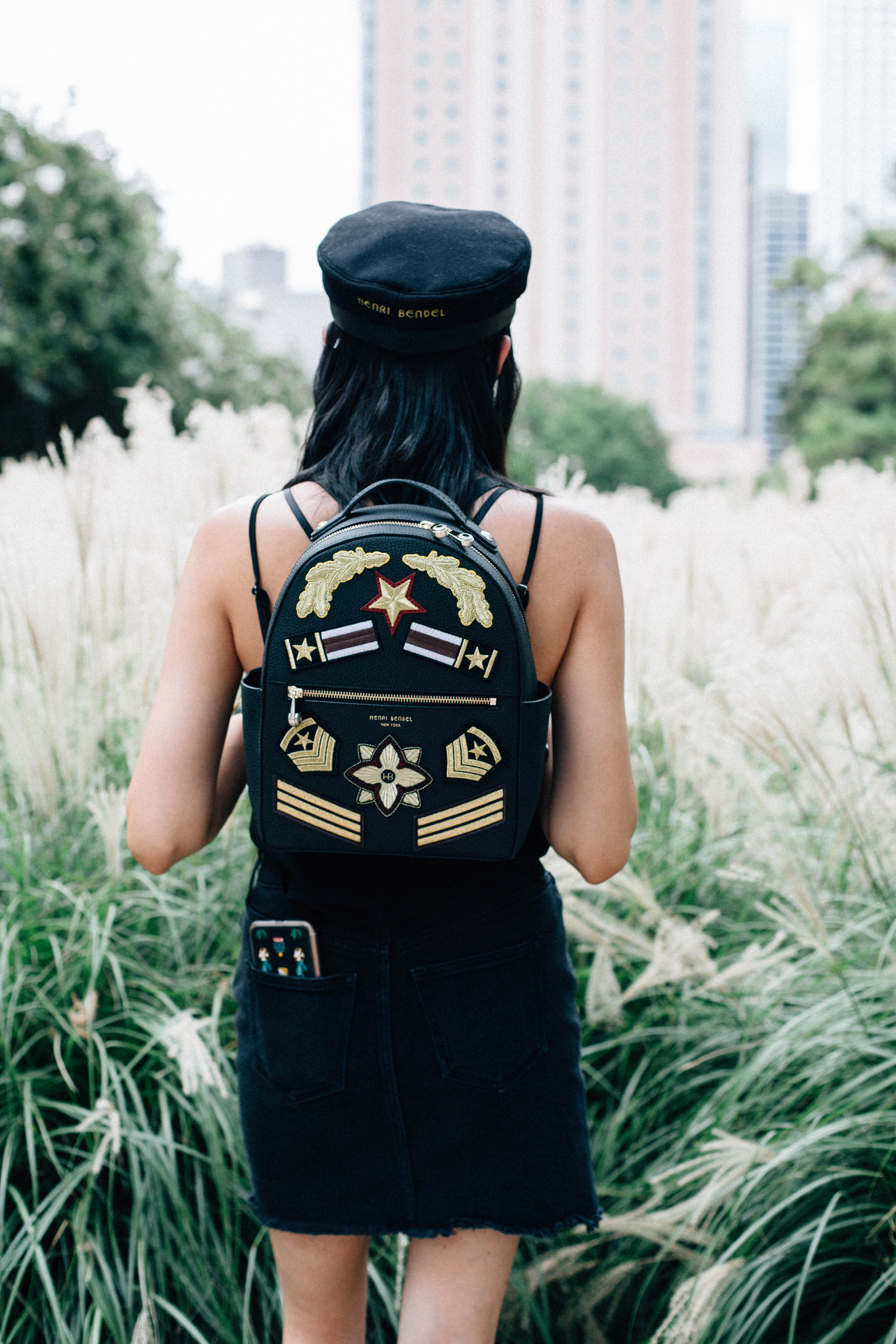 Lifestyle blogger Lilly Beltran of Daily Craving in a Henri Bendel backpack and newsboy hat
