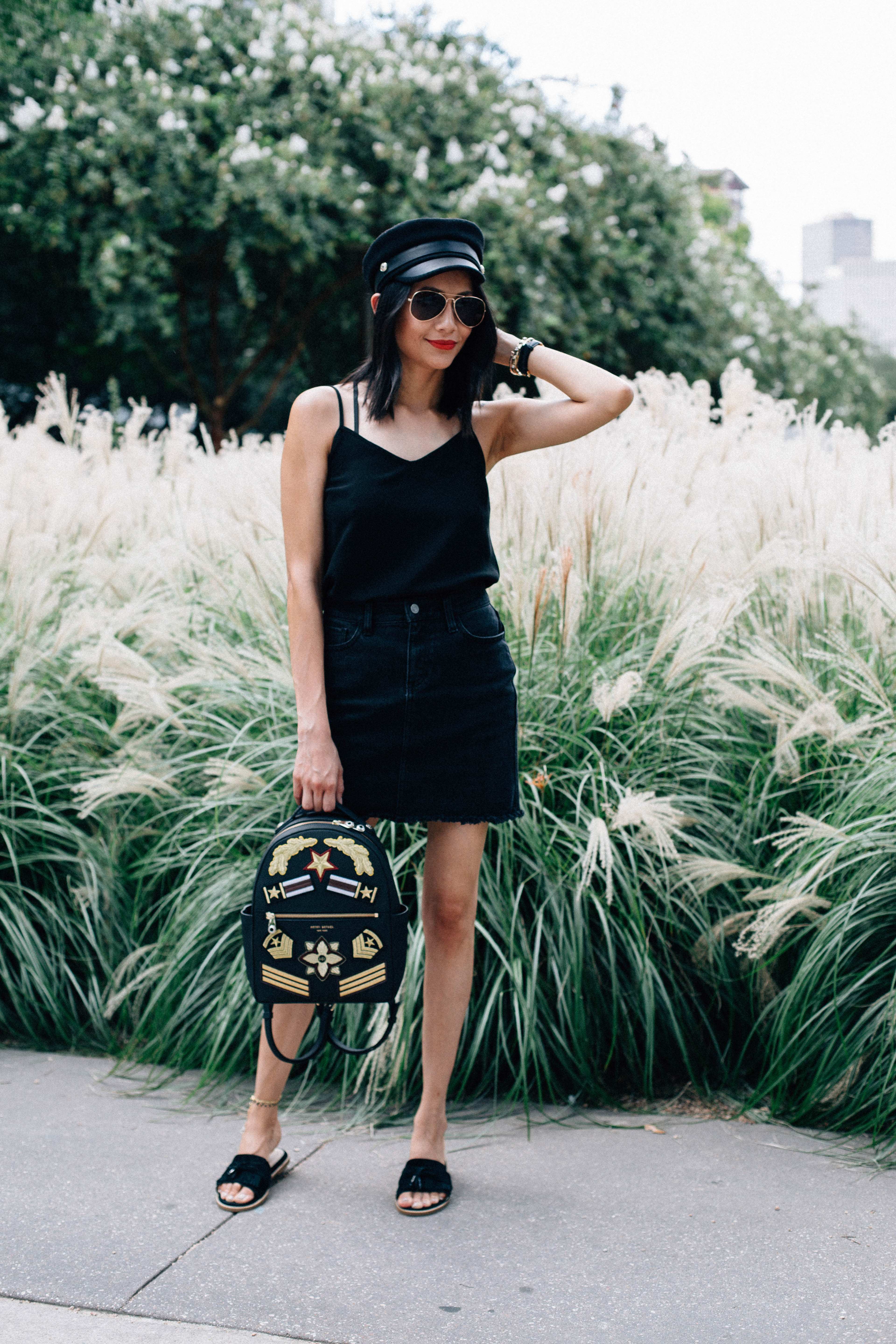 Lifestyle blogger Lilly Beltran of Daily Craving in an all black look with a denim skirt and newsboy hat
