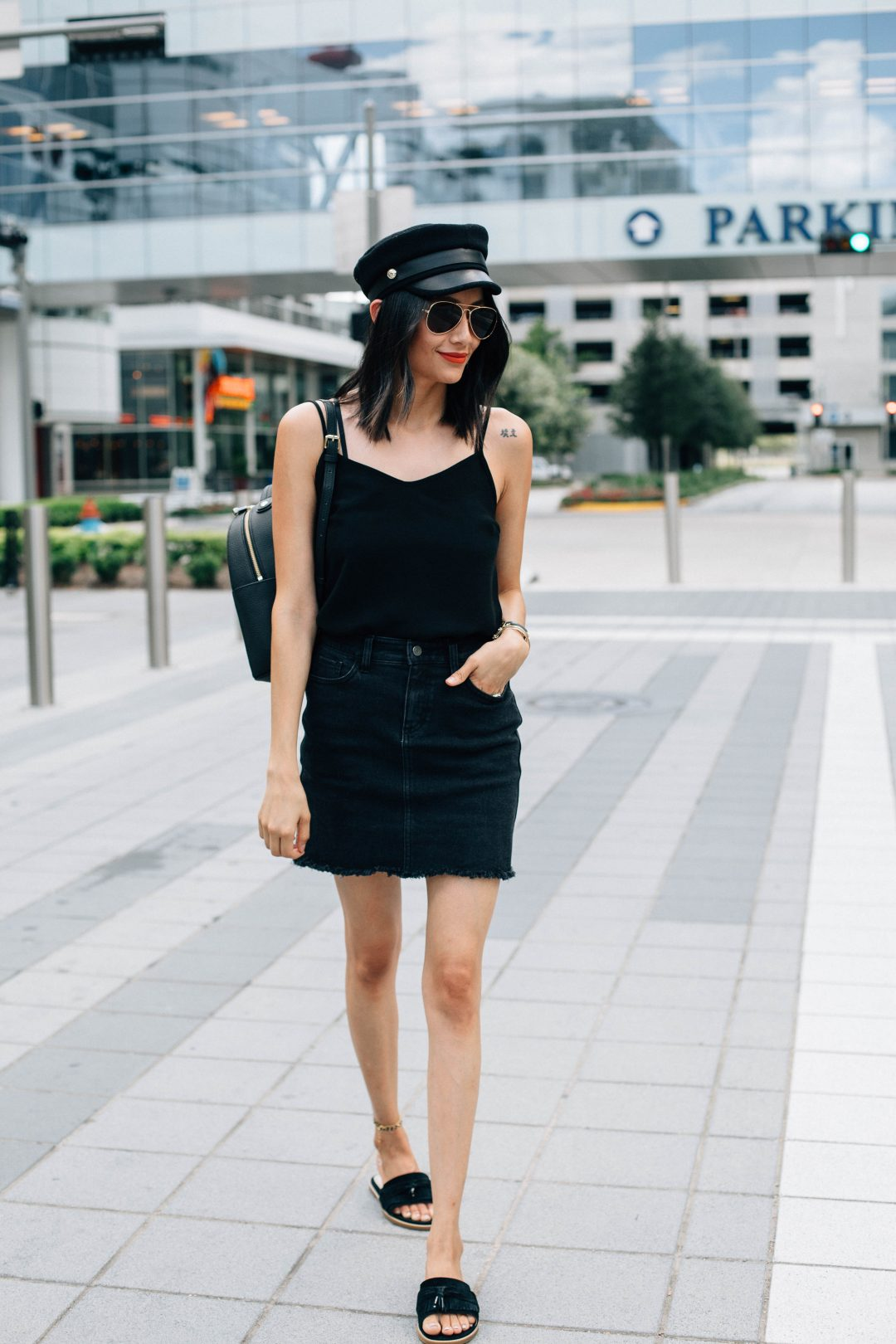 How to wear a newsboys hat | Military Style In black denim skirt, suede fringe slides & Henri Bendel military patches backpack