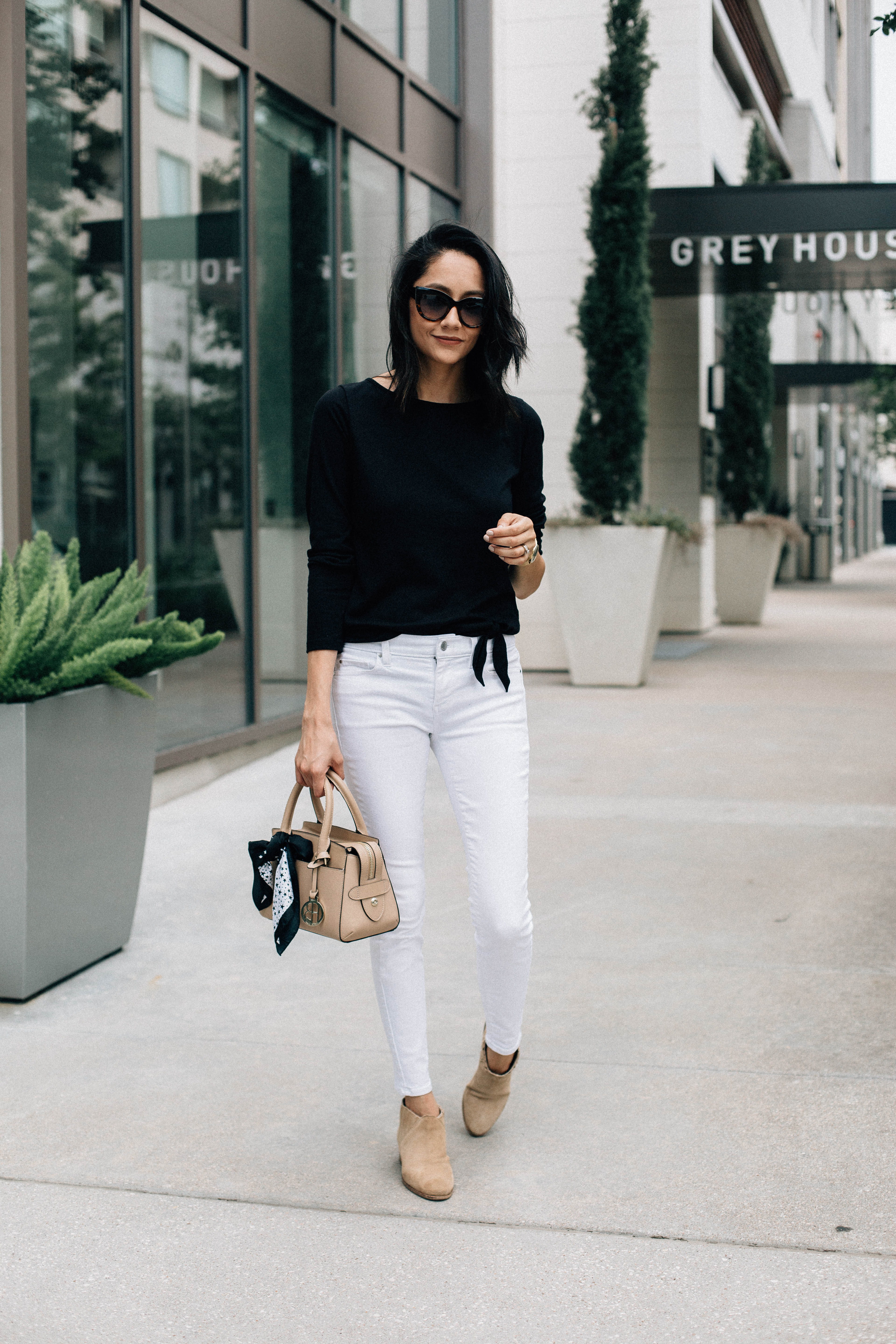 Lifestyle blogger Lilly Beltran of Daily Craving in a casual look wearing white jeans and a black tee