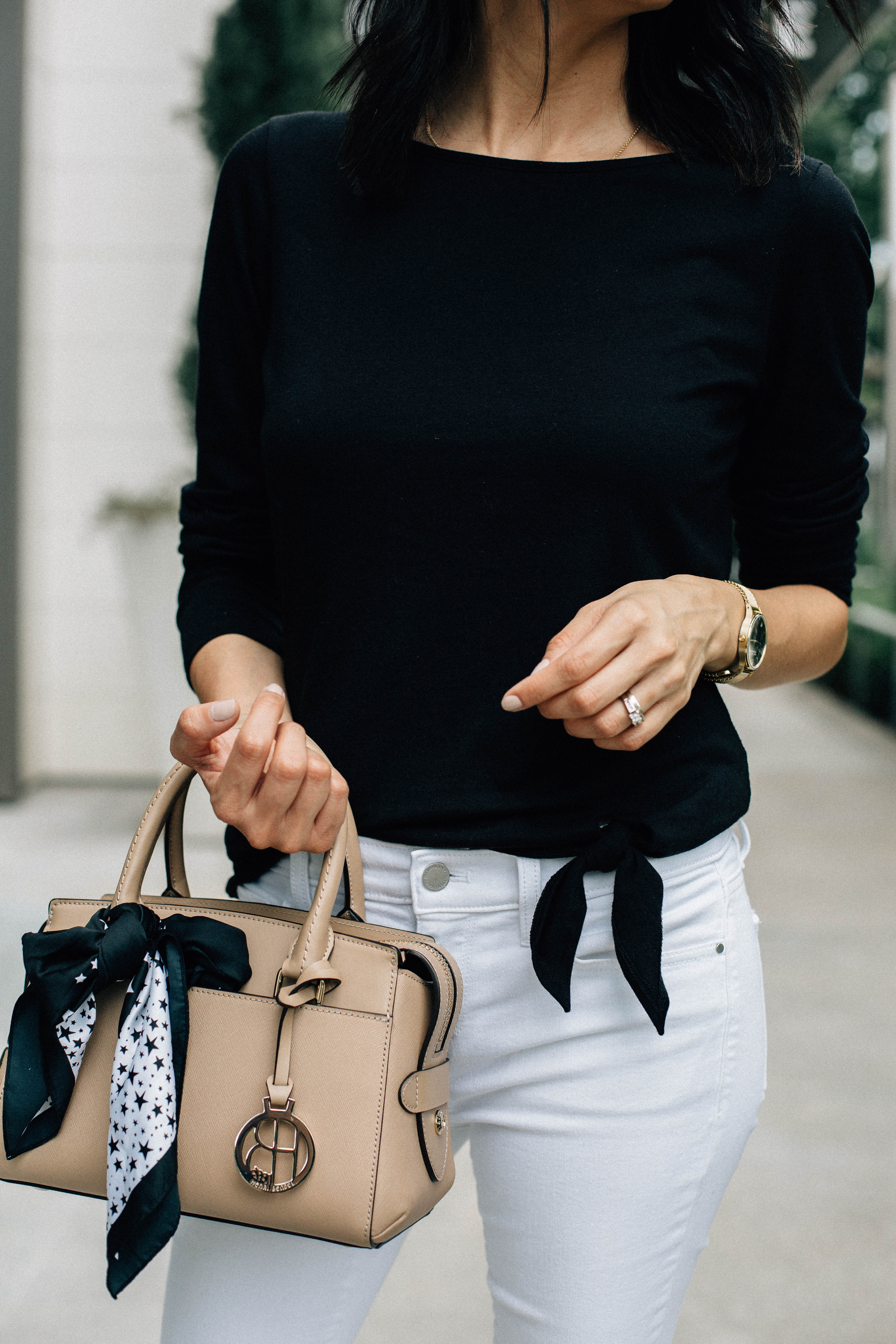 Lilly Beltran of Daily Craving blog wearing a Henri Bendel bag with a basic black tee