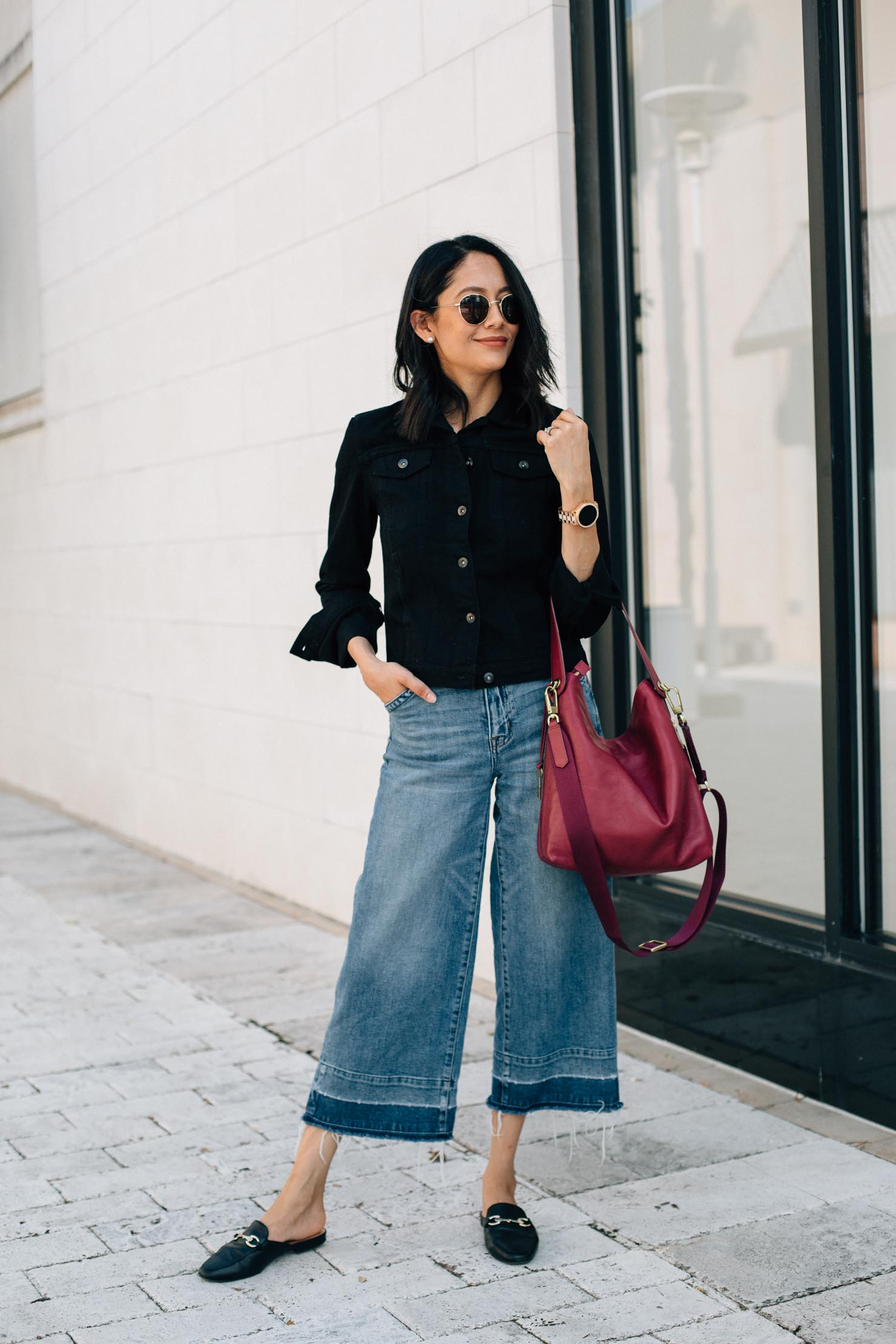 Lifestyle Blogger Lilly Beltran of Daily Craving in a casual look with wide leg denim a black denim jacket and Fossil bag