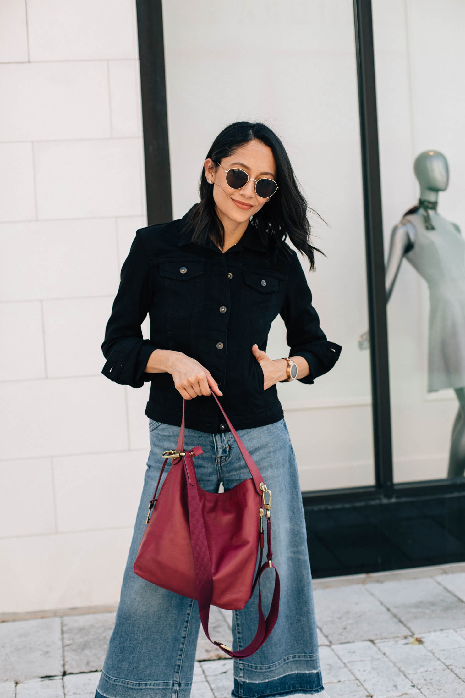 Lifestyle blogger Lilly Beltran wearing a casual fall outfit with a black denim jacket and round sunglasses