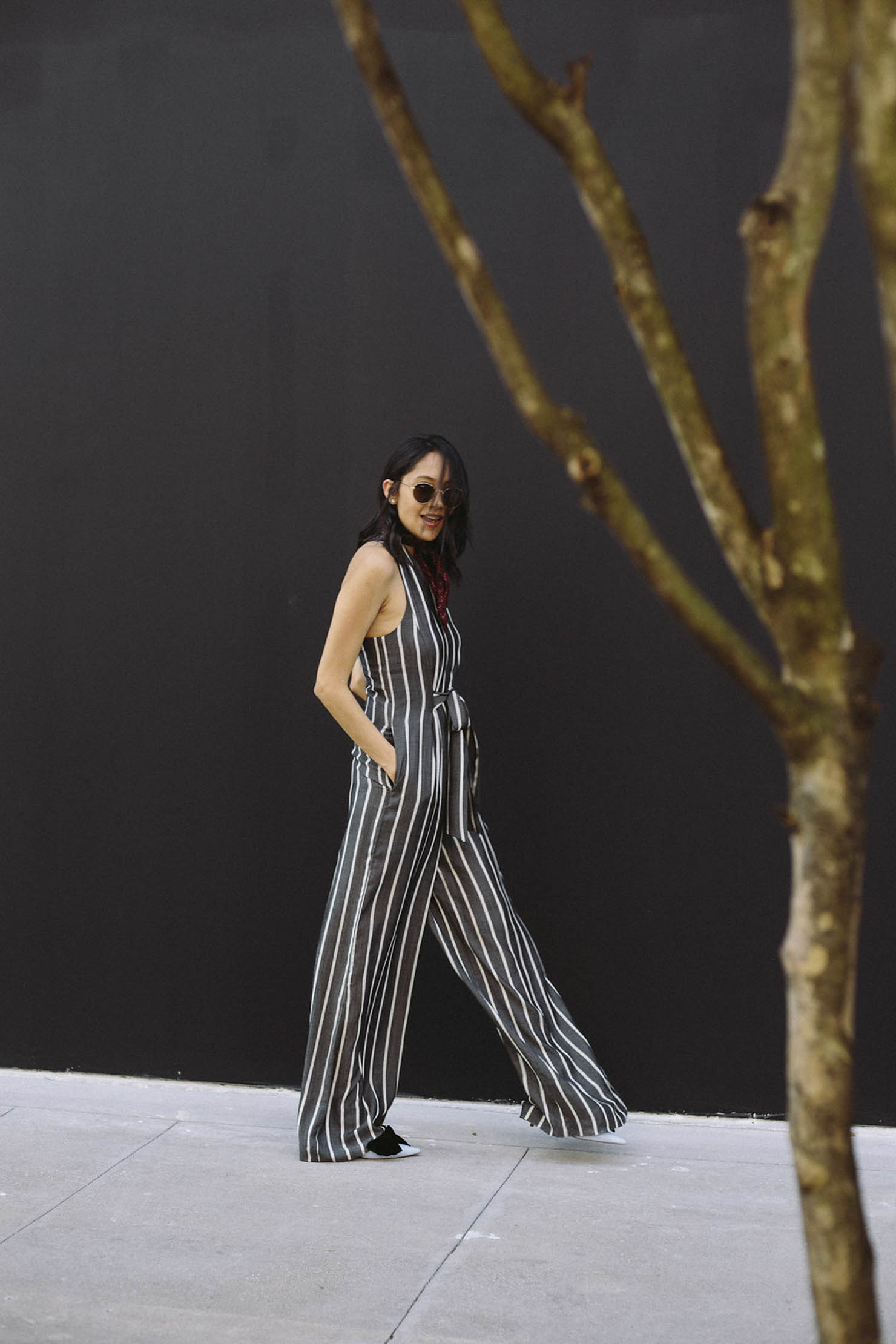 Style blogger Lilly Beltran of Daily Craving in a casual look wearing a Rachel Roy striped jumpsuit