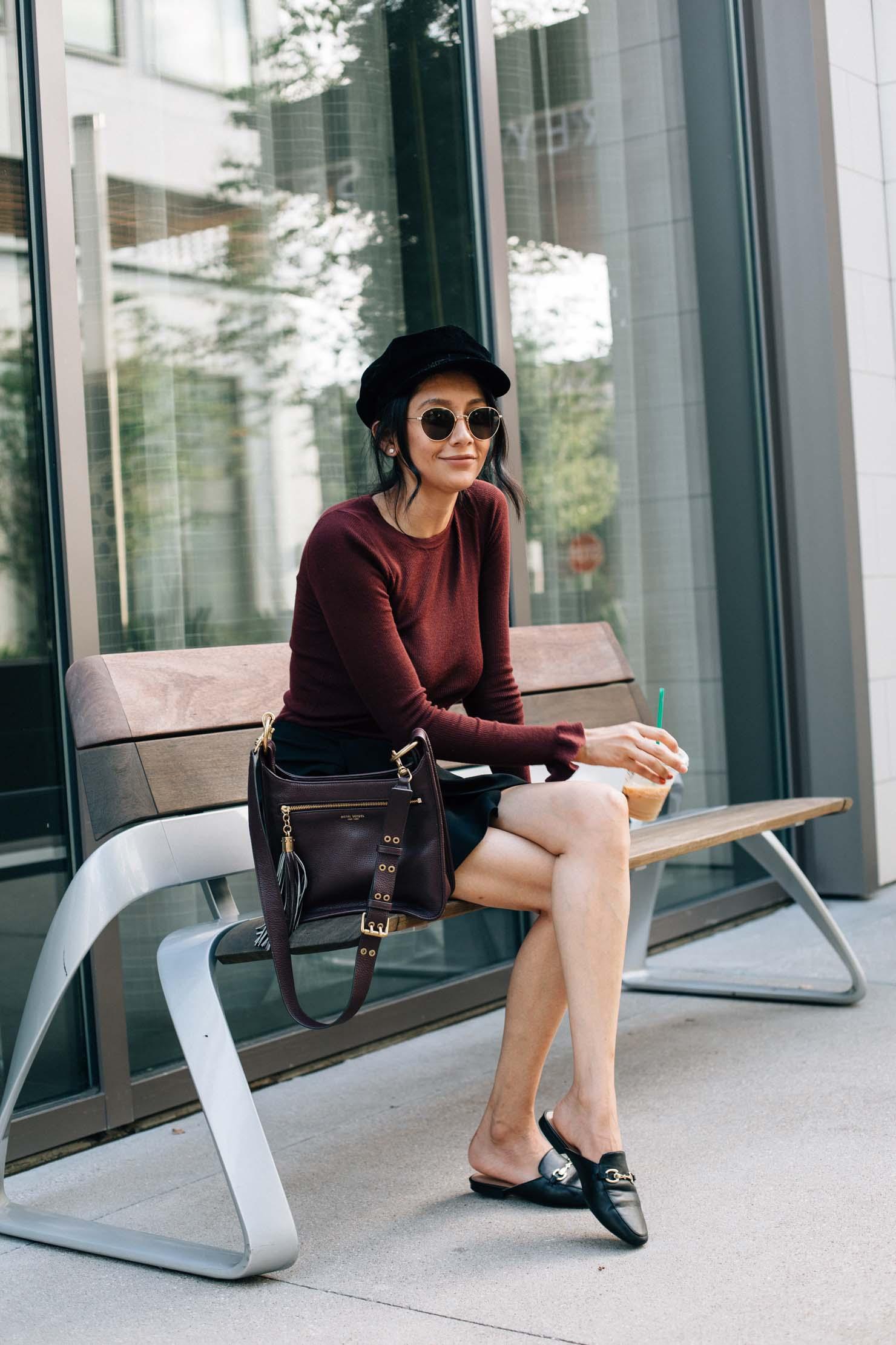 Style blogger Lilly Beltran wearing a baker bot hat, ruffle sleeve sweater and Henri Bendel bag