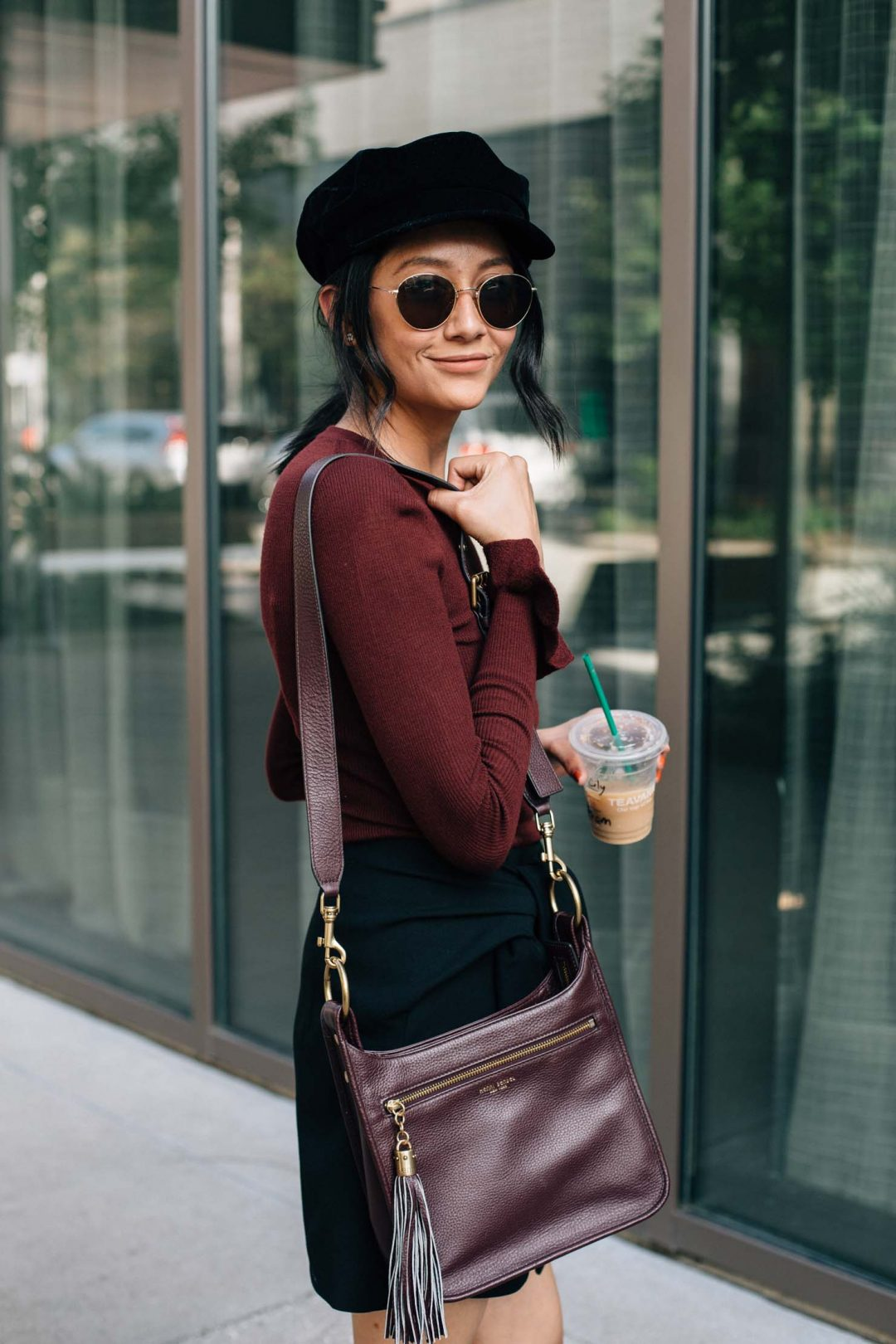 Lilly Beltran of Daily Craving blog wearing a burgundy sweater with ruffle sleeves and a black wrap skirt with a baker boy hat