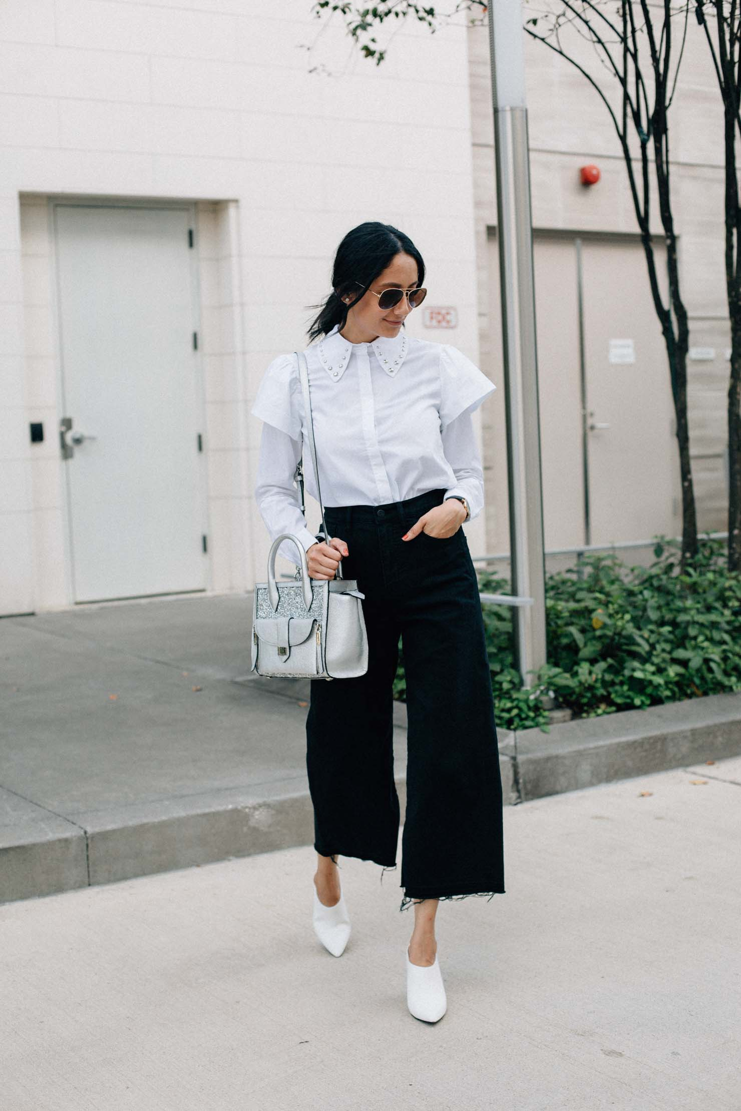 Lilly Beltran of style blog Daily Craving wearing white mules, black culottes and white ruffle sleeve top
