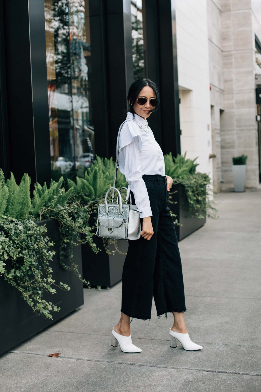Style blogger Lilly Beltran wearing white mules with black culotte pants and white ruffle sleeve shirt