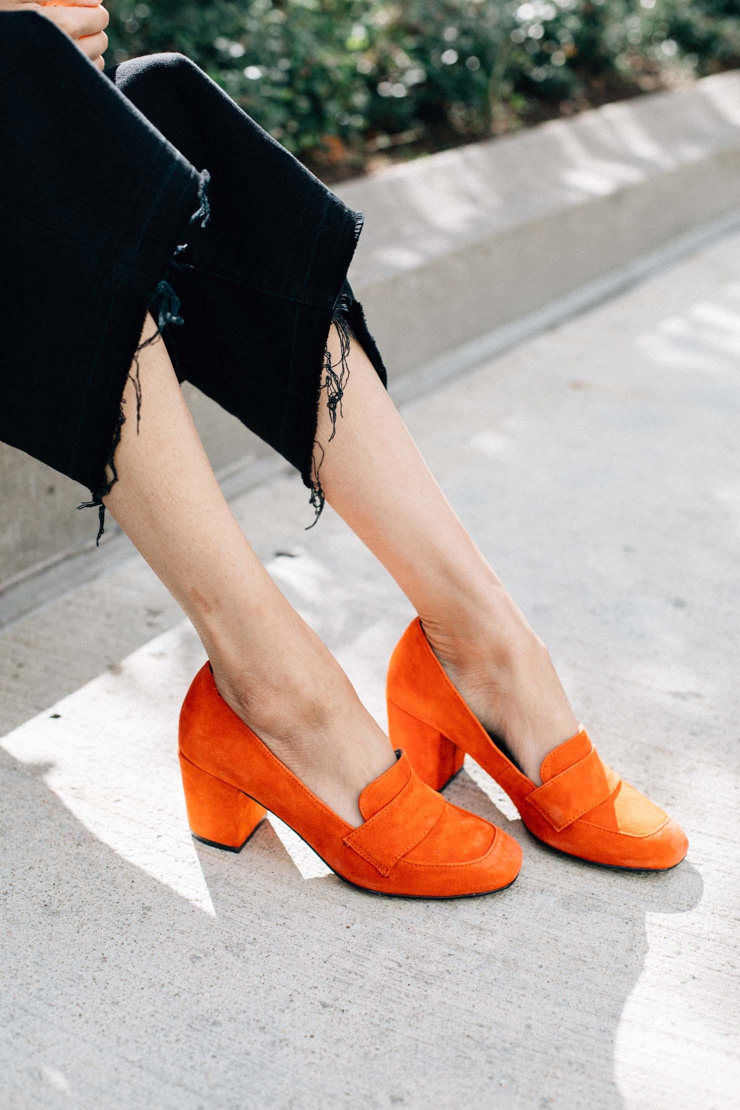 Style blogger Lilly Beltran wearing red block heel pumps and black raw hem denim